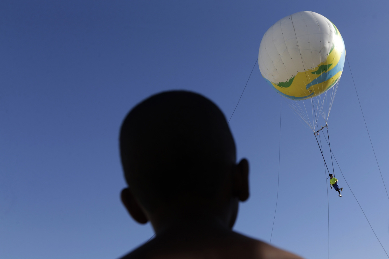A boy observes as an artist from Cia. Base circus group hangs on a balloon while performing in their show  Futebol Voador  during the International Circus Festival in Vila Cruzeiro slum in Rio de Janeiro May 12, 2014.