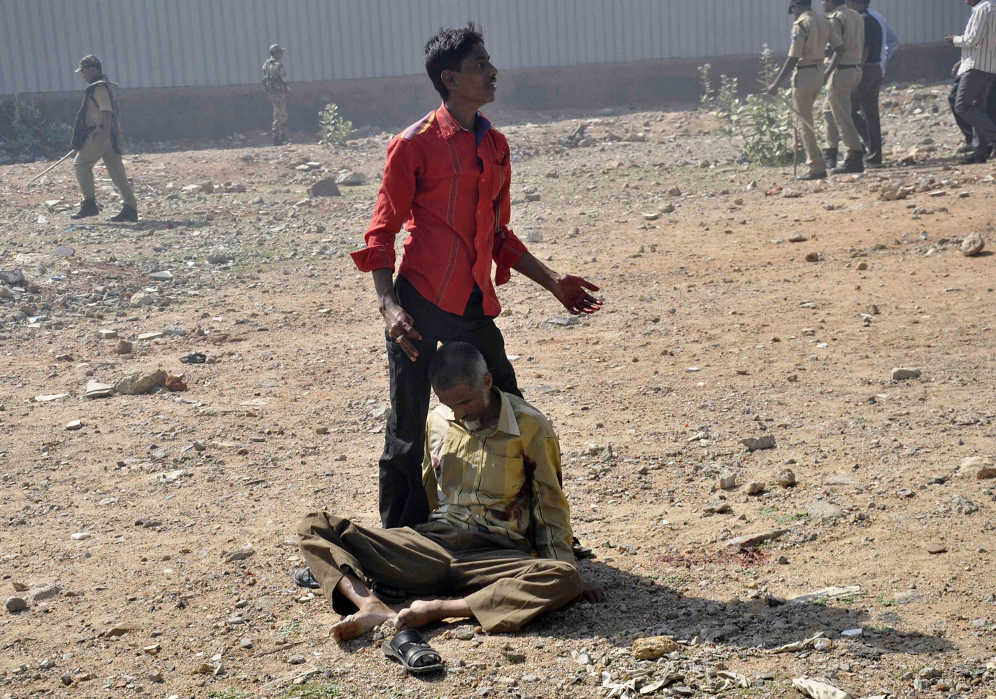 May 14, 2014. A man calls for help to carry his injured father to a hospital after clashes between two communities on the outskirts of the southern Indian city of Hyderabad.