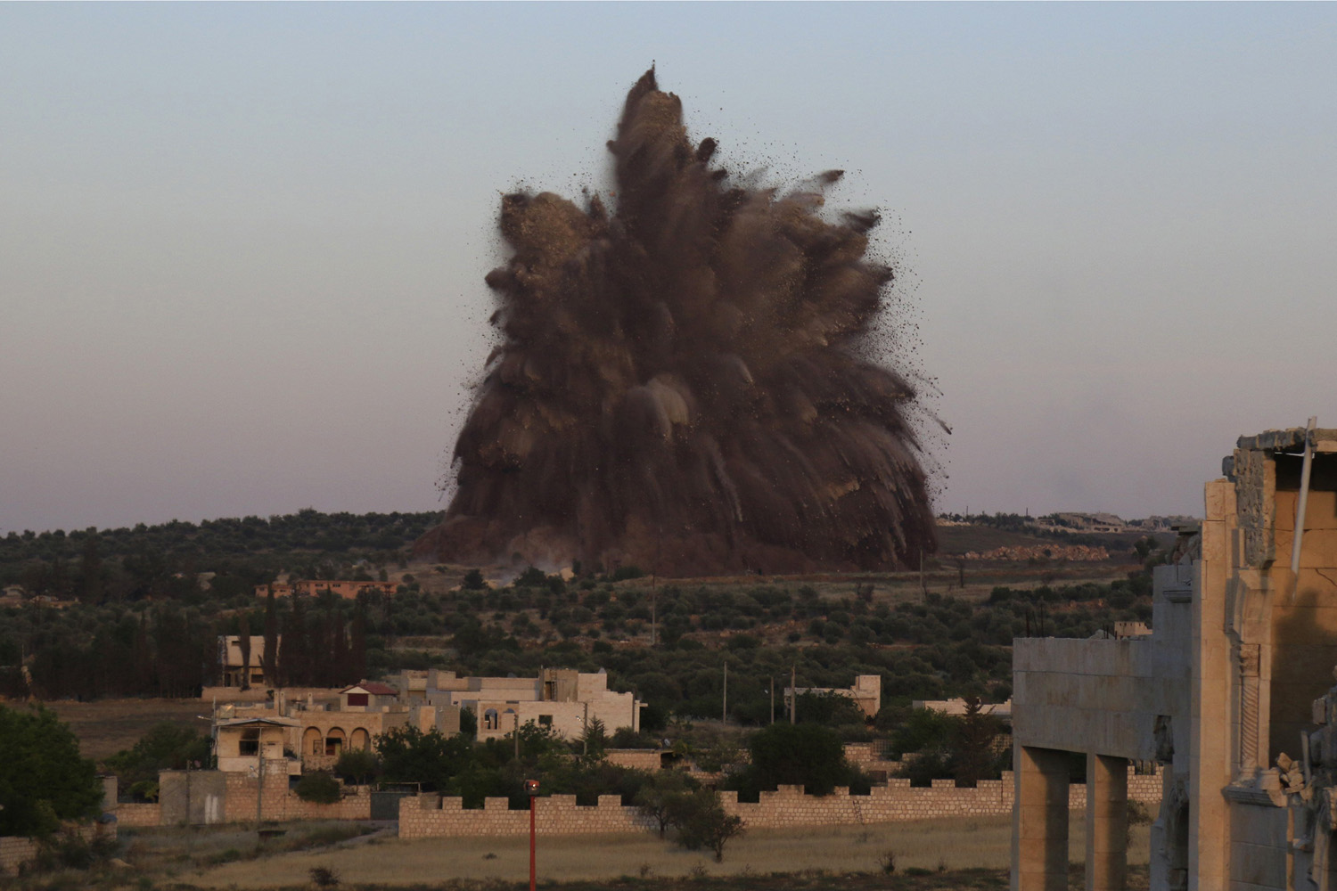 May 14, 2014. Debris rises during what rebel fighters said was an operation in which they blew up a tunnel targeting the regime's al-Sawadi checkpoint, in Idlib province.