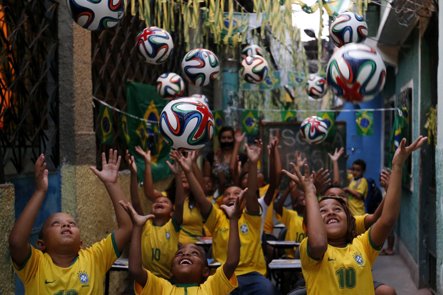 Children throw official 2014 FIFA World Cup soccer balls into the air during a protest against the 2014 World Cup, organized by the NGO Rio de Paz at the Jacarezinho slum in Rio de Janeiro on May 14, 2014.
