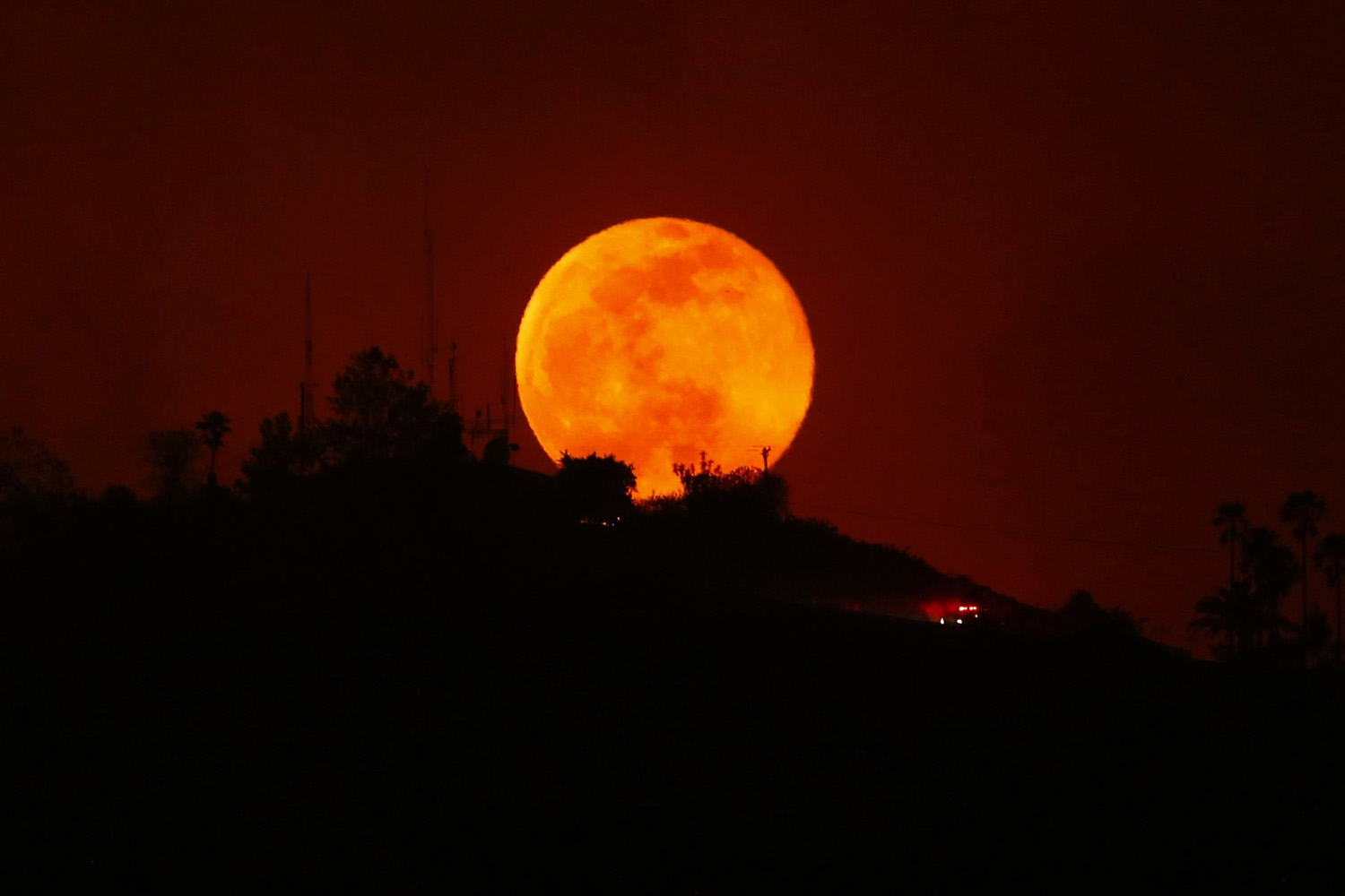 May 14, 2014. An emergency vehicle makes its way past a rising moon as it travels along a burned-out hillside near San Marcos, California.