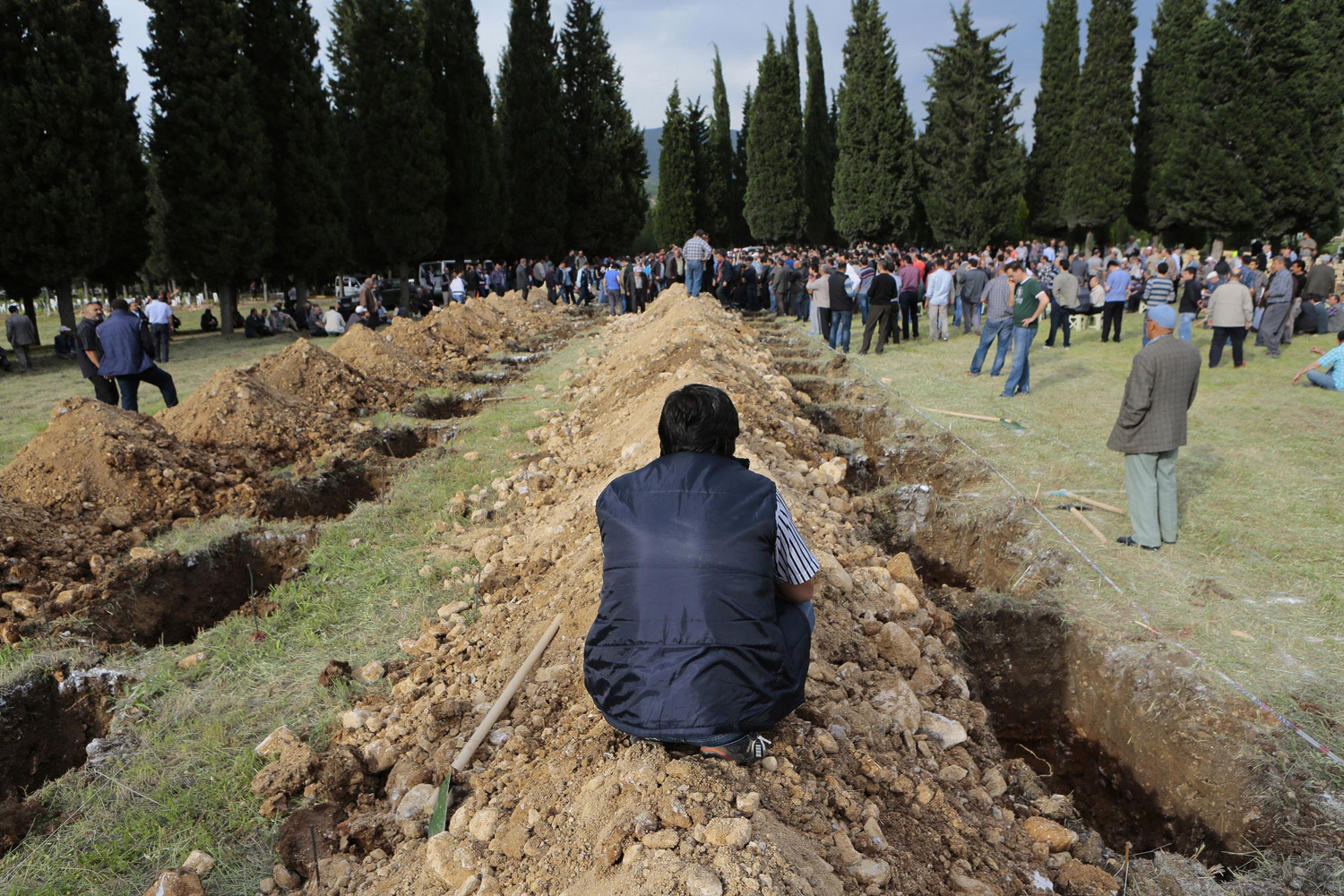 May 14, 2014. A man sits near graves during the funeral of a miner who died in a fire at a coal mine, at a cemetery in Soma, a district in Turkey's western province of Manisa.