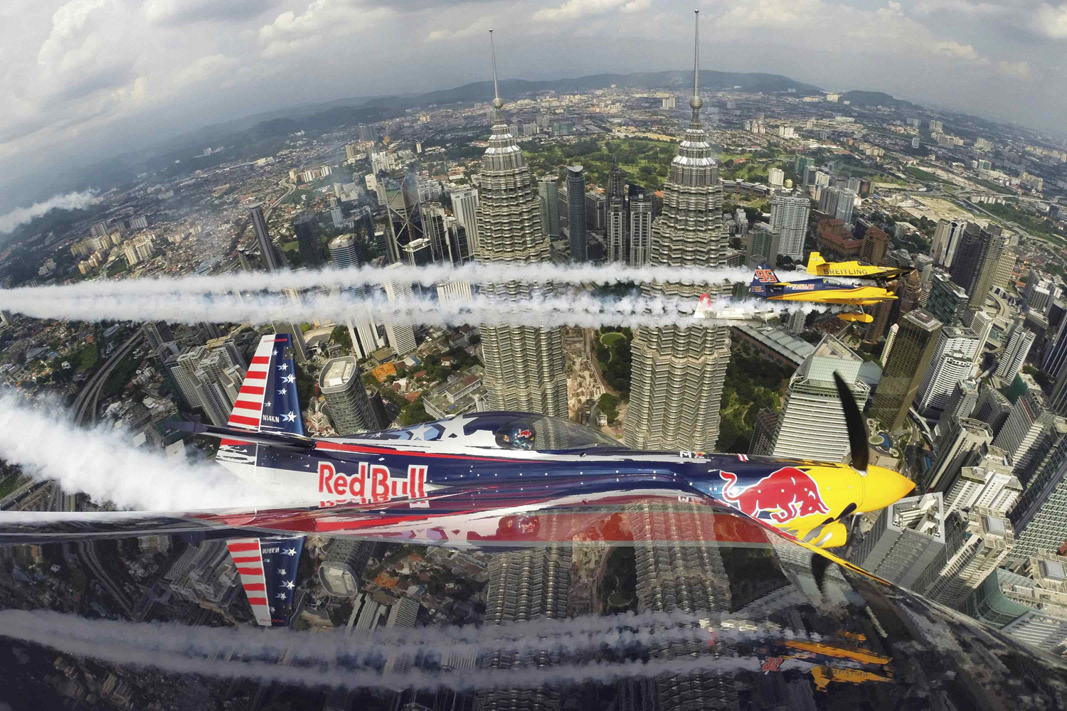 Kirby Chambliss of the U.S. flies in formation with Matt Hall of Australia, Yoshihide Muroya of Japan and Nigel Lamb of Britain prior to the third stage of the Red Bull Air Race World Championship in front of the Petronas Towers in Kuala Lumpur May 15, 2014.