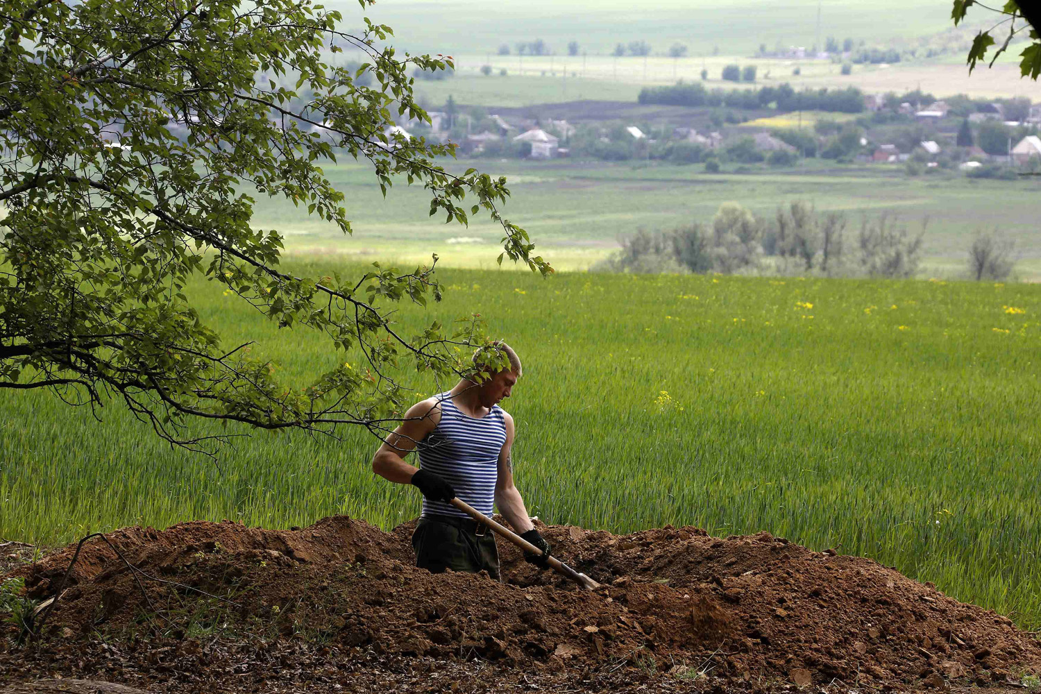 May 15, 2014. A Ukrainian soldier digs a trench outside Bylbasivka.