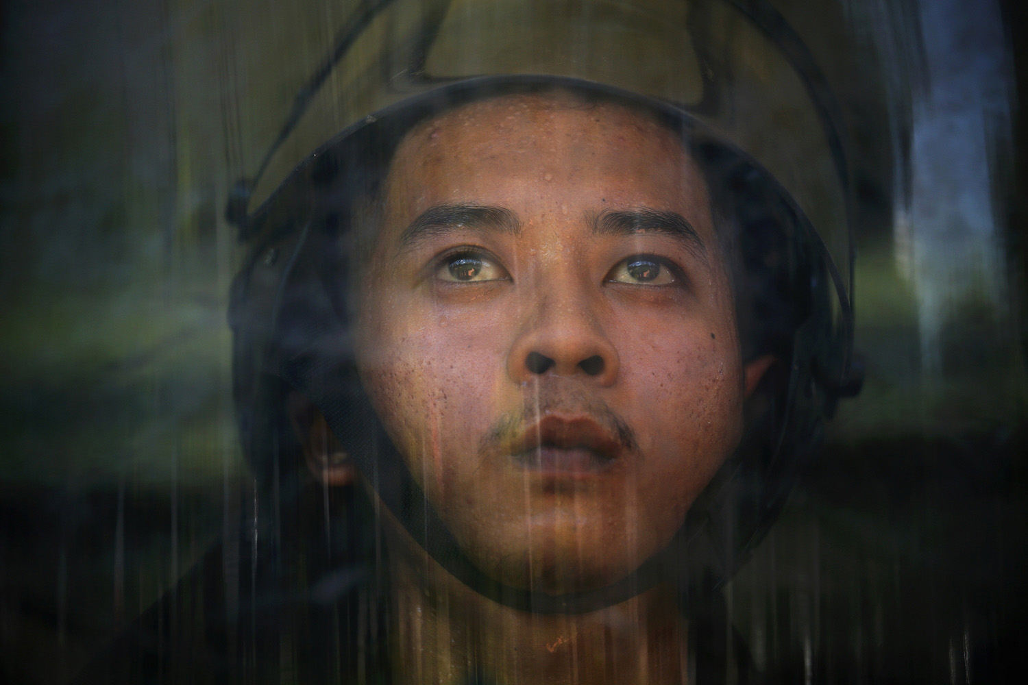 May 15, 2014. A member of an Air Force military force perspires behind his shield after anti-government protesters broke into an air force base in Bangkok, Thailand.