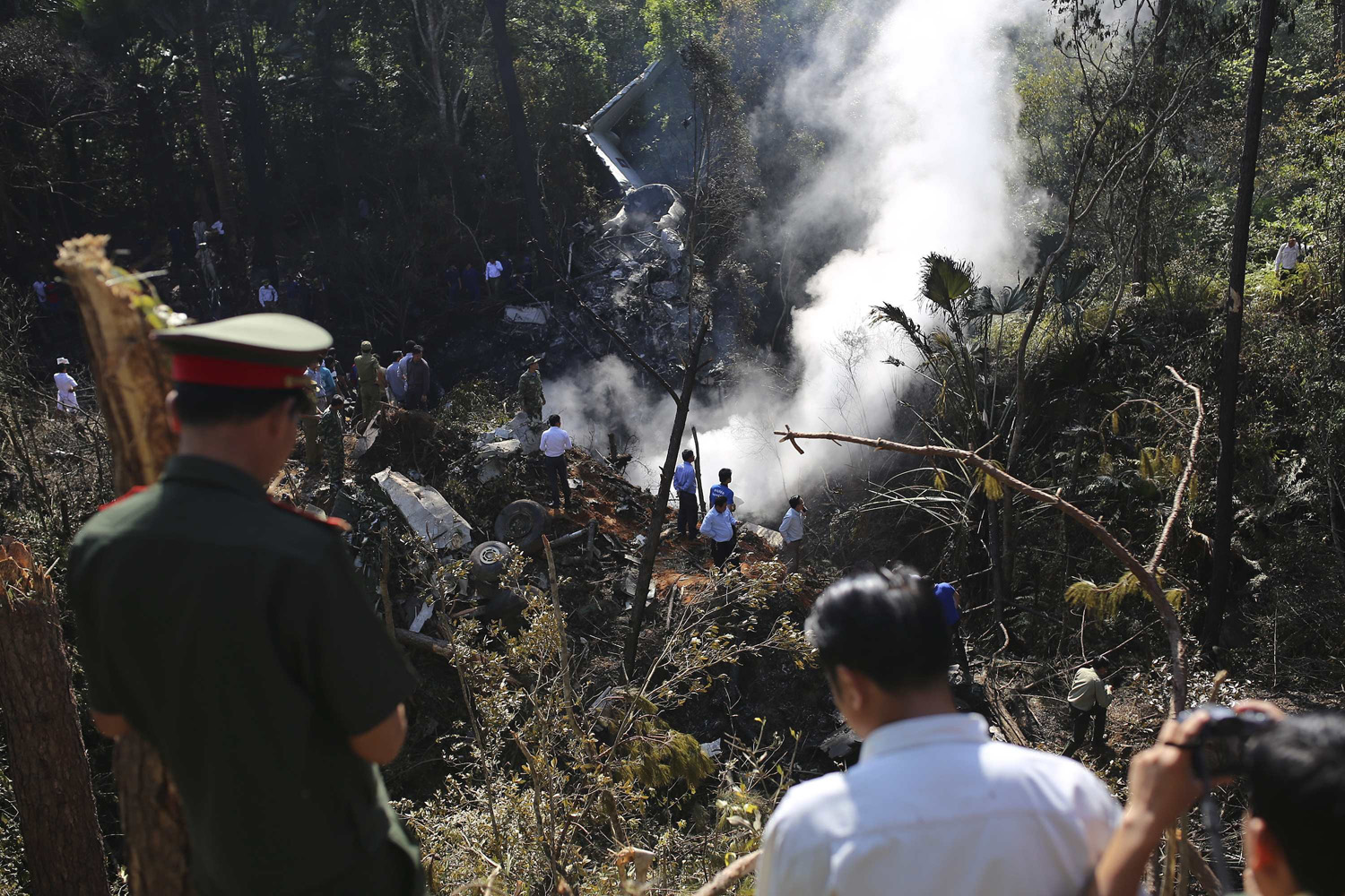 May 17, 2014. Rescue workers search an air force plane crash site near Nadee village, in Xiang Khouang province in the north of the country.