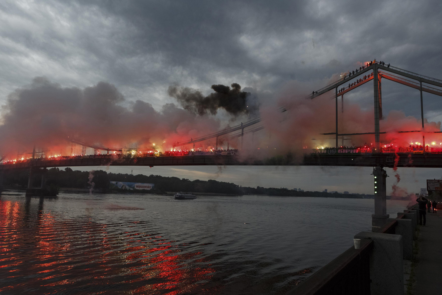 Ukrainian soccer fans light flares on a bridge across the Dnieper River in Kiev, Ukraine on May 18, 2014.