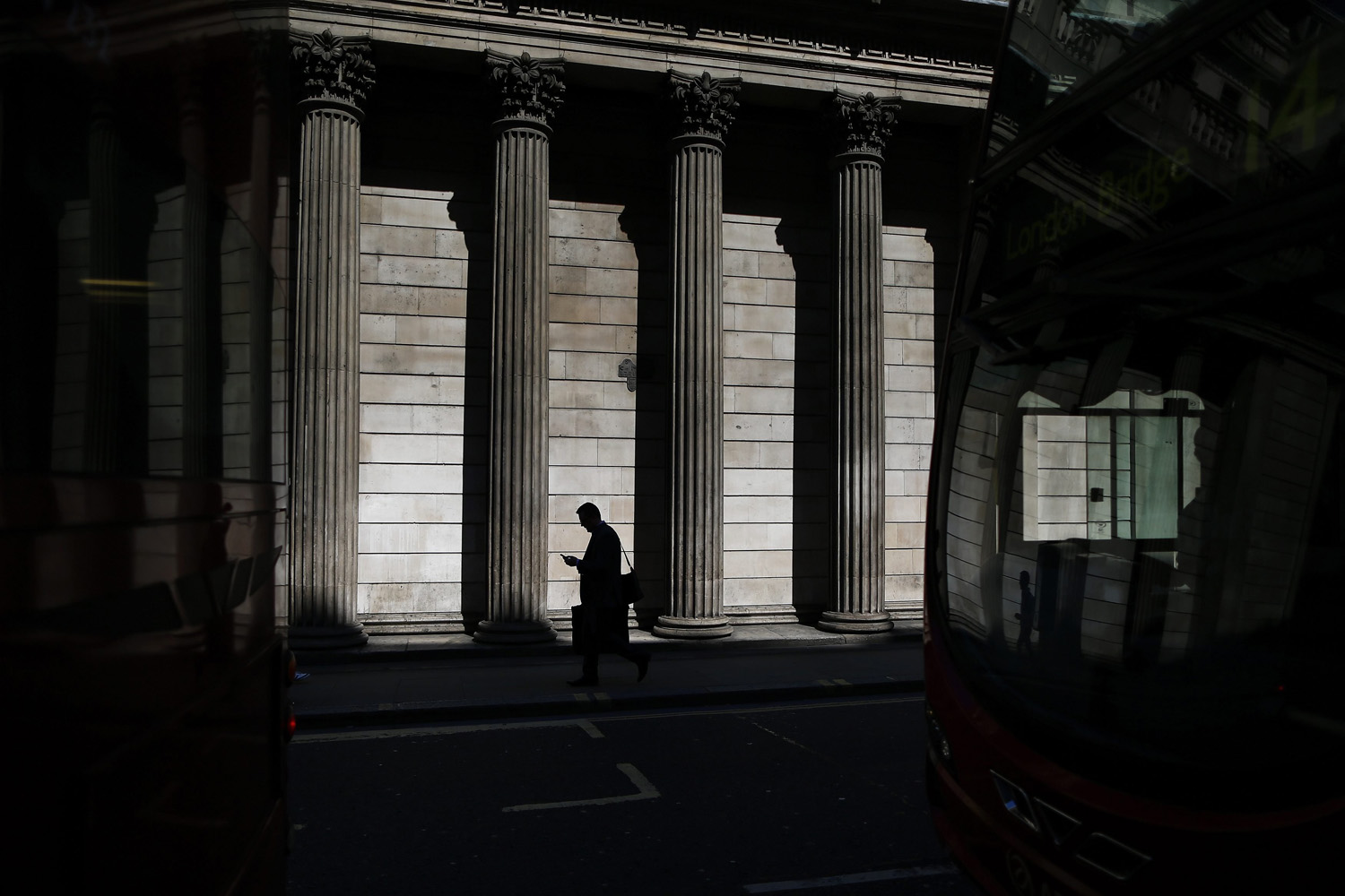 May 19, 2014. A man is reflected in a bus windscreen as he walks past the columns of the Bank of England on a sunny morning in the City of London.