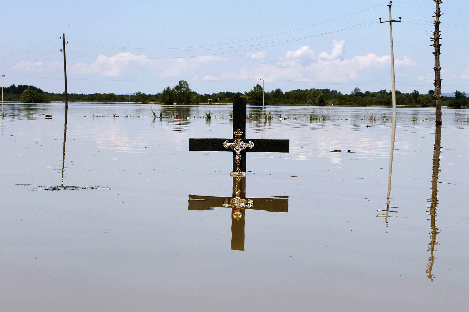 May 19, 2014. A cross is seen in flood waters at a cemetery during heavy floods in the village of Vojskova.