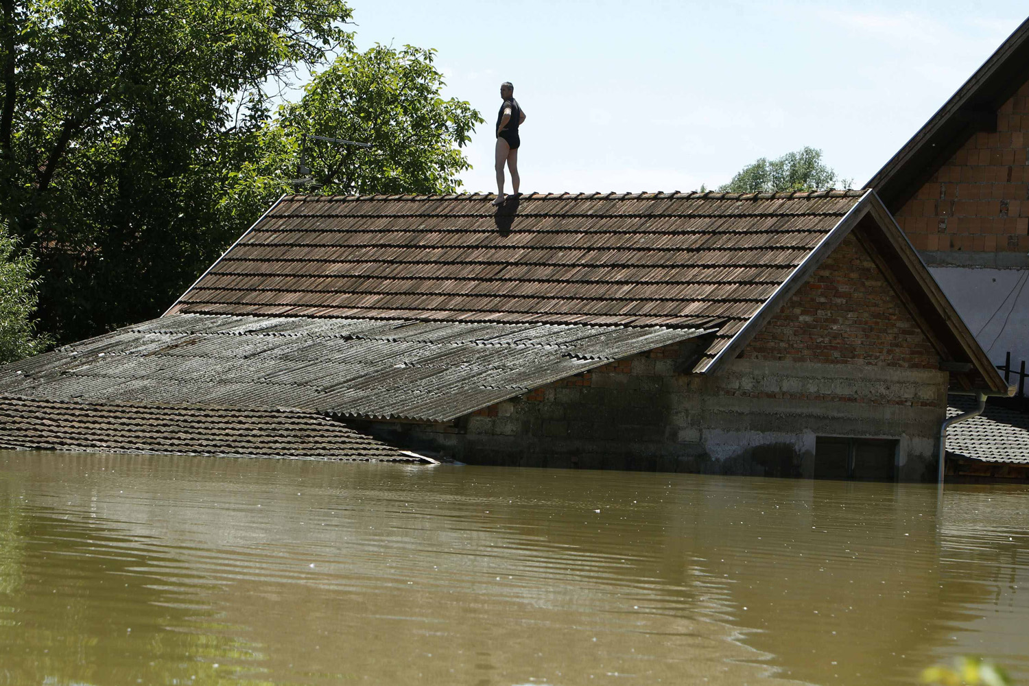 May 19, 2014. A man waits to be rescued from his house during heavy floods in Vojskova  More than a quarter of Bosnia's four million people have been affected by the worst floods to hit the Balkans in more than a century, the government said on Monday.