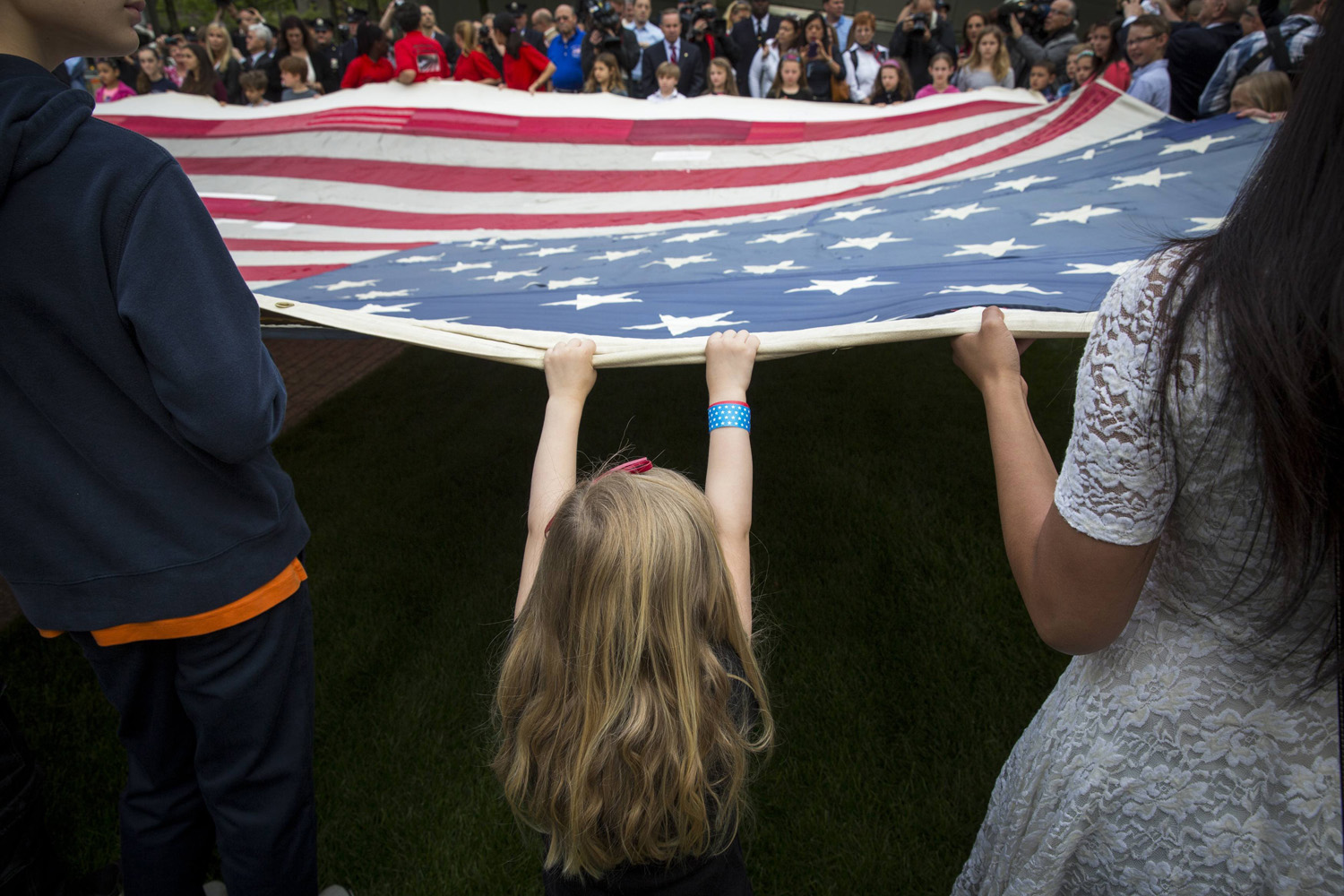 May 21, 2014. A girl designated to assist with transferring the National 9/11 Flag, donated by New York Says Thank You Foundation, holds it aloft on the grounds of the 9/11 Memorial Plaza before donating it to the National September 11 Memorial Museum in New York.