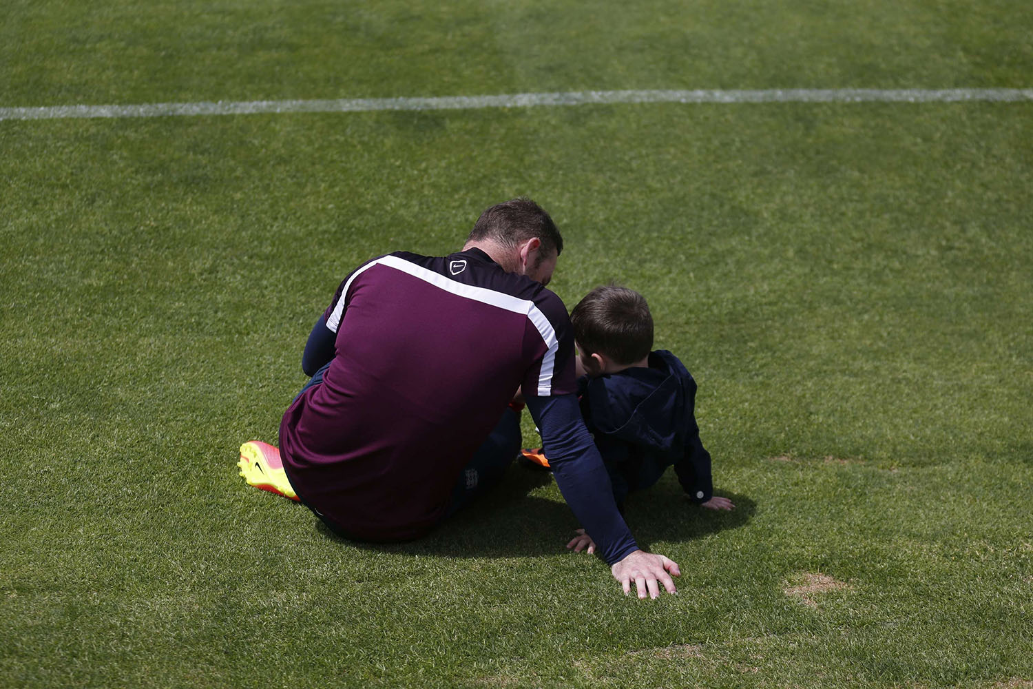 England's national soccer team player Wayne Rooney speaks with his son, Kai, after a training session in Almancil, near Faro in Portugal, on May 21, 2014.