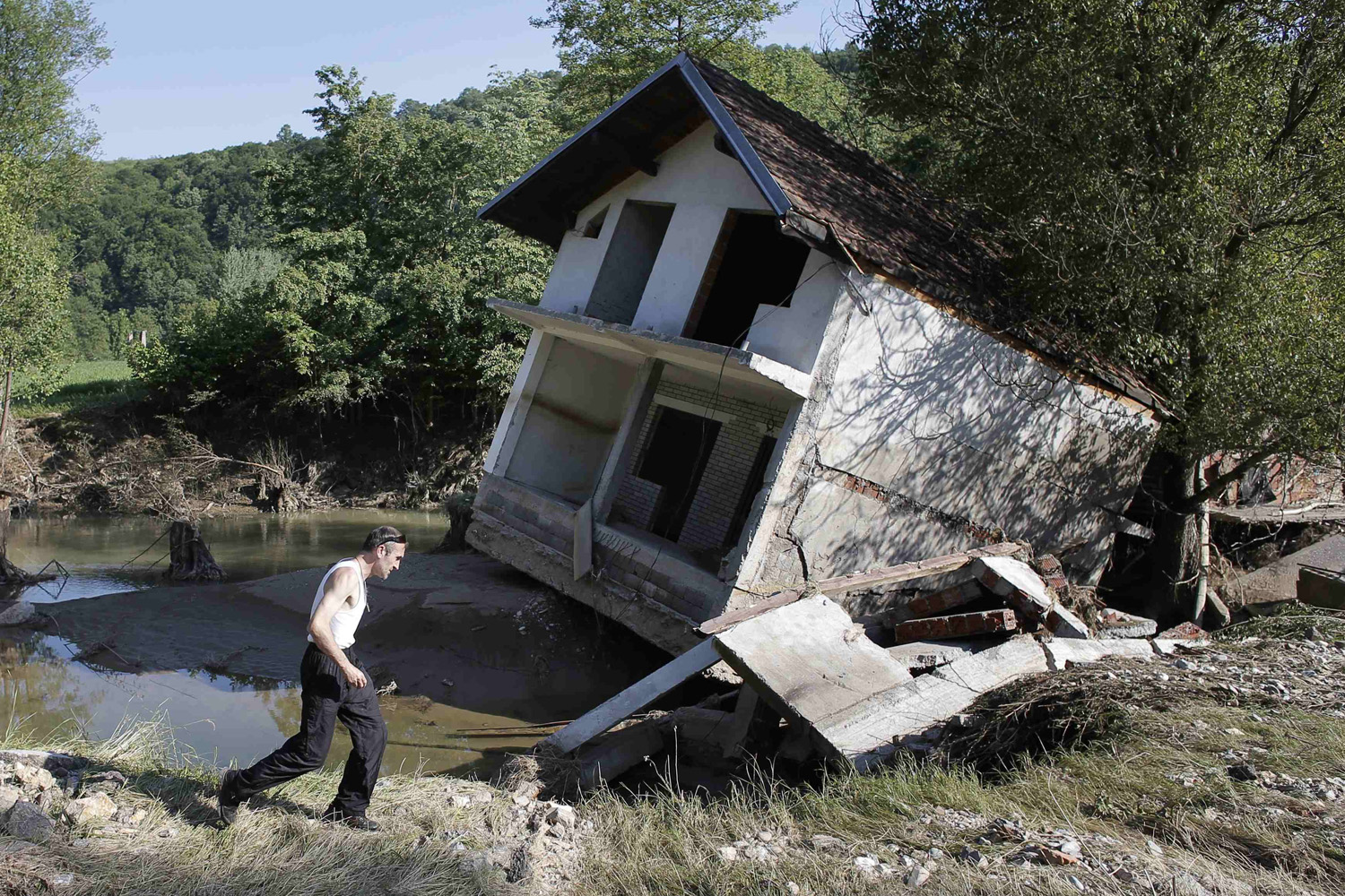 May 21, 2014. A man walks past a house tilted by floods in the town of Valjevo, southwest from Belgrade.