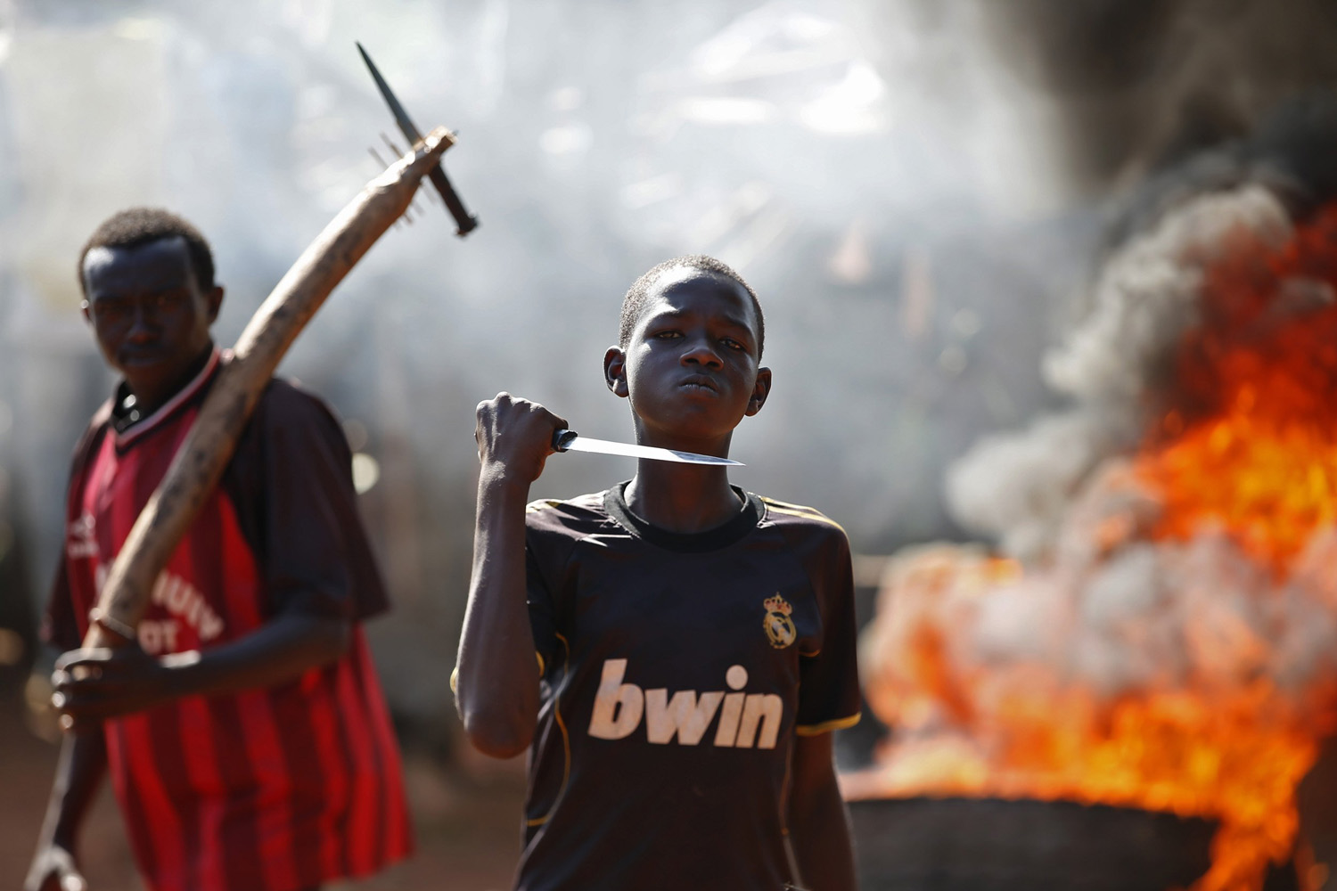 May 22, 2014. A boy gestures in front of a barricade on fire during a protest after French troops opened fire at protesters blocking a road in Bambari, Central African Republic.