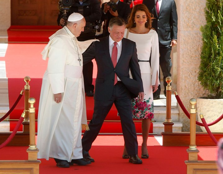Jordan's King Abdullah and Queen Rania walk with Pope Francis during a welcoming ceremony in Amman
