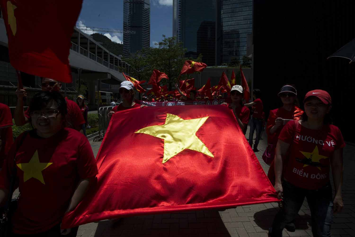 Hong Kong based Vietnamese demonstrators carry Vietnam's flag during a protest against China's territory claim in Hong Kong May 25, 2014. Around 200 people marched on Sunday to declare Paracel Islands belong to Vietnam. REUTERS/Tyrone Siu (CHINA - Tags: POLITICS CIVIL UNREST TPX IMAGES OF THE DAY)