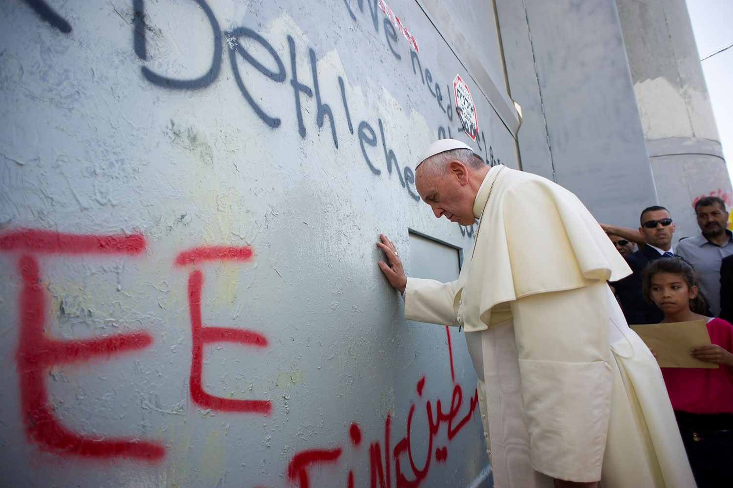 Pope Francis touches the wall that divides Israel from the West Bank, on his way to celebrate a mass in Manger Square, in the West Bank city of Bethlehem on May 25, 2014