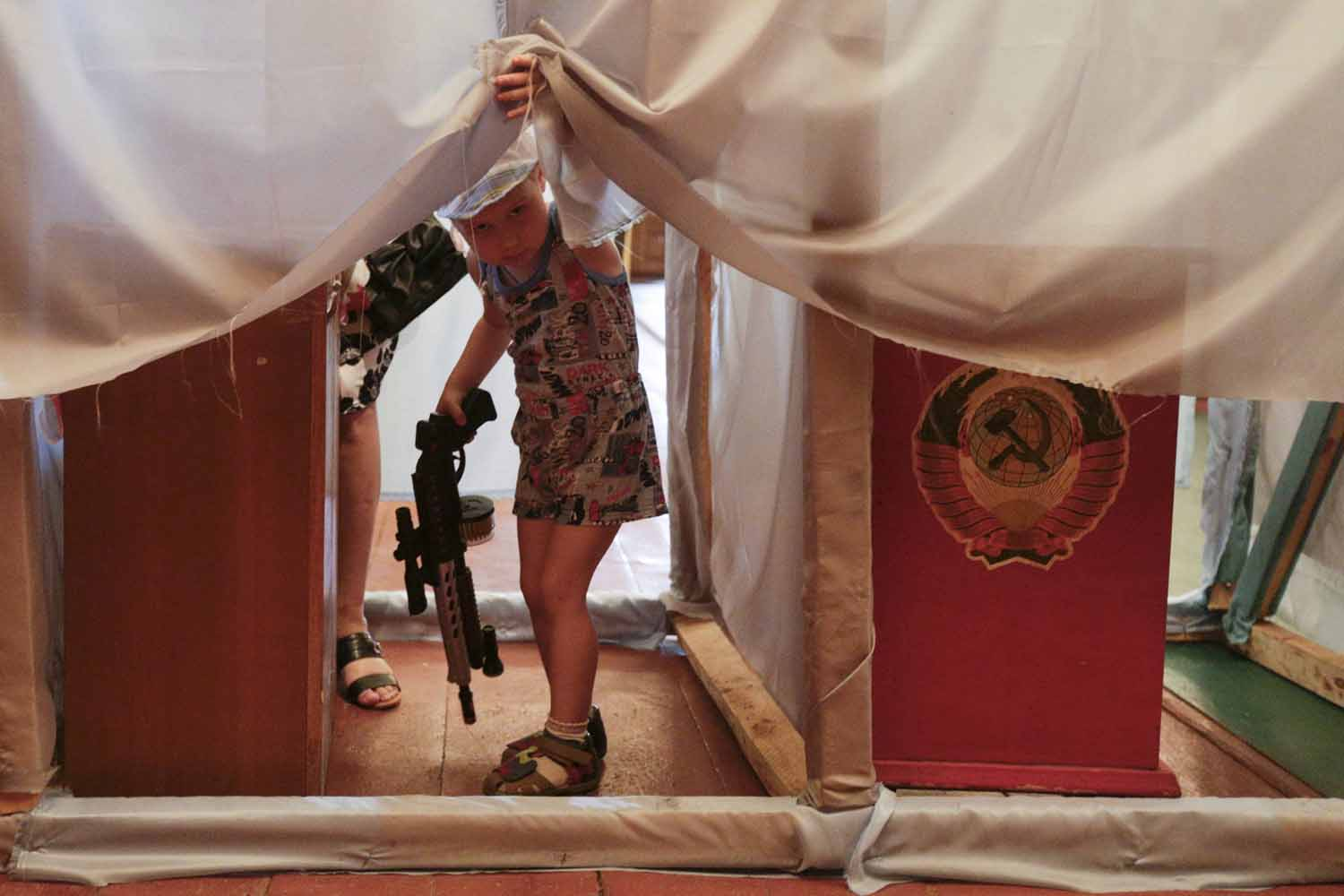 May 25, 2014. A child looks out as voters fill out ballot papers in booths during voting in a presidential election at a polling station in the village of Kodra in North Ukraine.