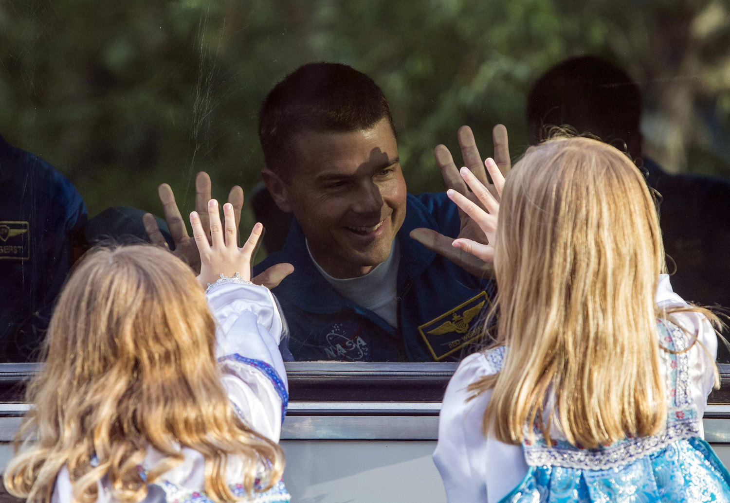 Reid Wiseman of the U.S., a member of the International Space Station crew, waves to his daughters from a bus before departure for a final pre-launch preparation at the Baikonur cosmodrome on May 28, 2014.