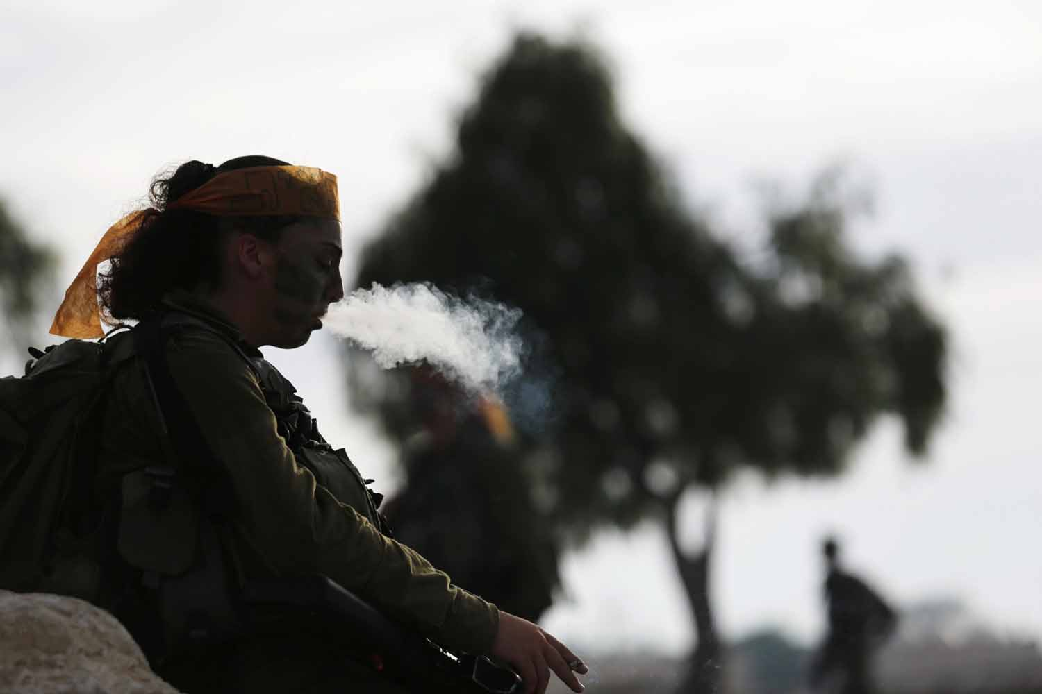 May 29, 2014. A female Israeli soldier of the Caracal battalion smokes after finishing a 20-kilometre march in Israel's Negev desert, near Kibbutz Sde Boker, marking the end of their training.