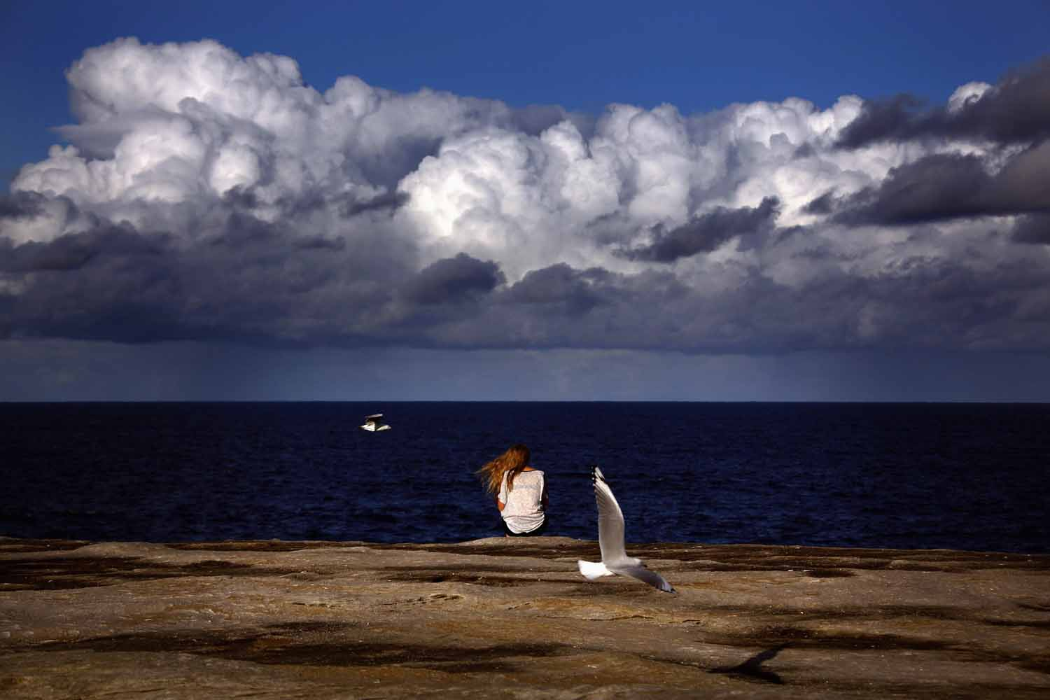 May 30, 2014.  Seagulls fly past a woman sitting on a rock ledge above Clovelly Beach on an autumn day in Sydney, Australia.