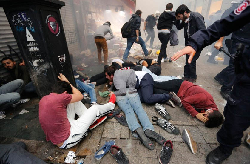 Anti-government protesters lie on the ground after riot police fired teargas to disperse them in central Istanbul