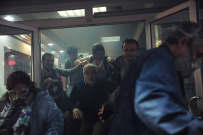 People try to escape from a cafe, after tear gas fired by riot police outside to disperse protesters seeped in, at central Istanbul