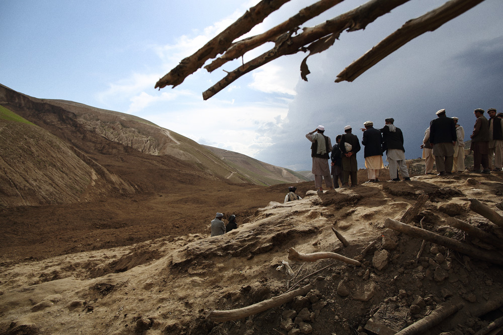 Men from the village look over the site of the landslide from a mound of mud that made its way up the adjacent side of the valley, May 3, 2014.