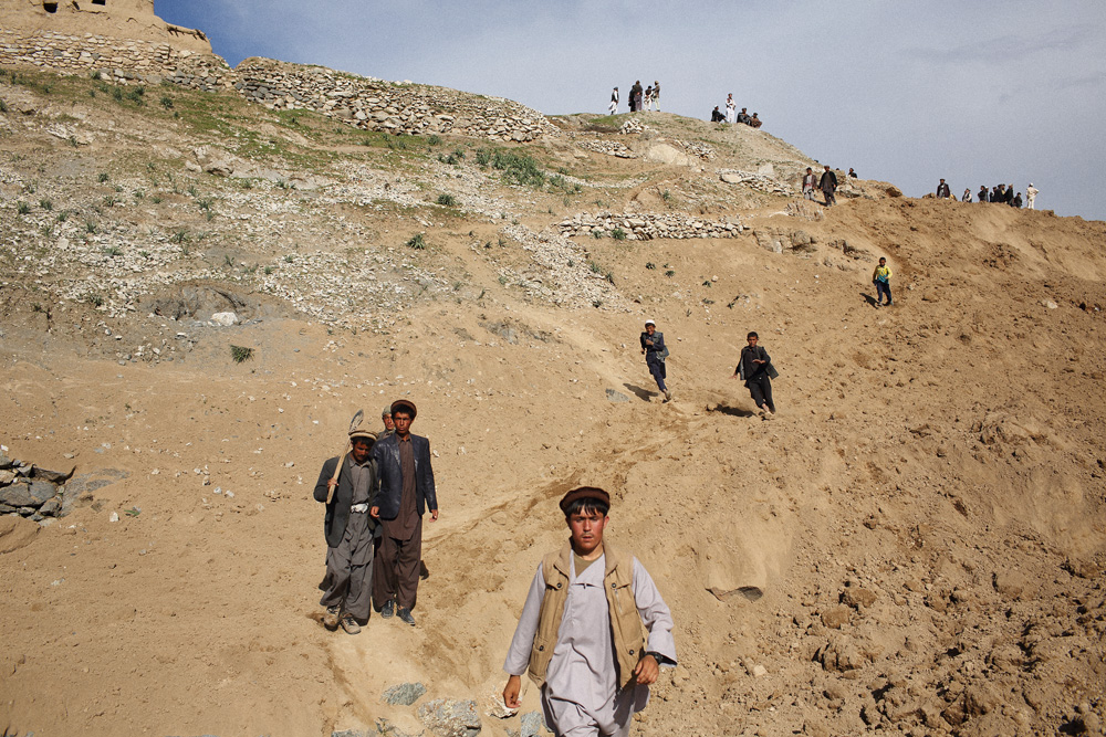 Men and boys - some carrying shovels - walk over mountains of dirt after visiting Argo district on foot from a nearby village to see if they could help in the rescue effort, May 3, 2014.