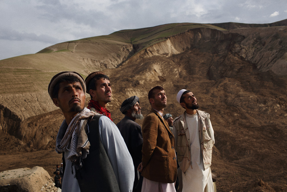 With the landslide in the background, men look to the sky as an Afghan National Army helicopter carrying Mohammad Karim Khalili, one of Afghanistan's two Vice Presidents, flies over the disaster, May 3, 2014.
