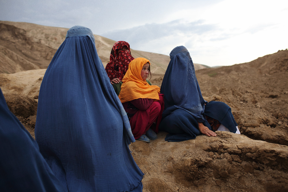 A group of women and a young girl mourn for their family members who were killed in yesterday's tragedy. The women sat, wailing on the mountains of mud above their homes buried below, May 3, 2014.