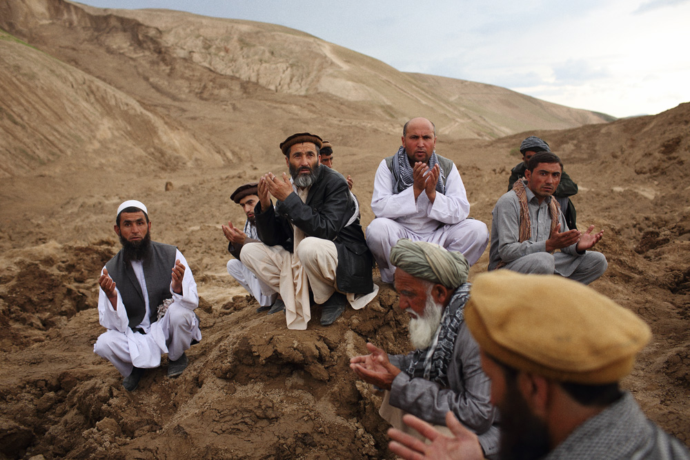Men gathered to offer prayers on the mountains of mud that buried many of their friends and relatives, May 3, 2014.