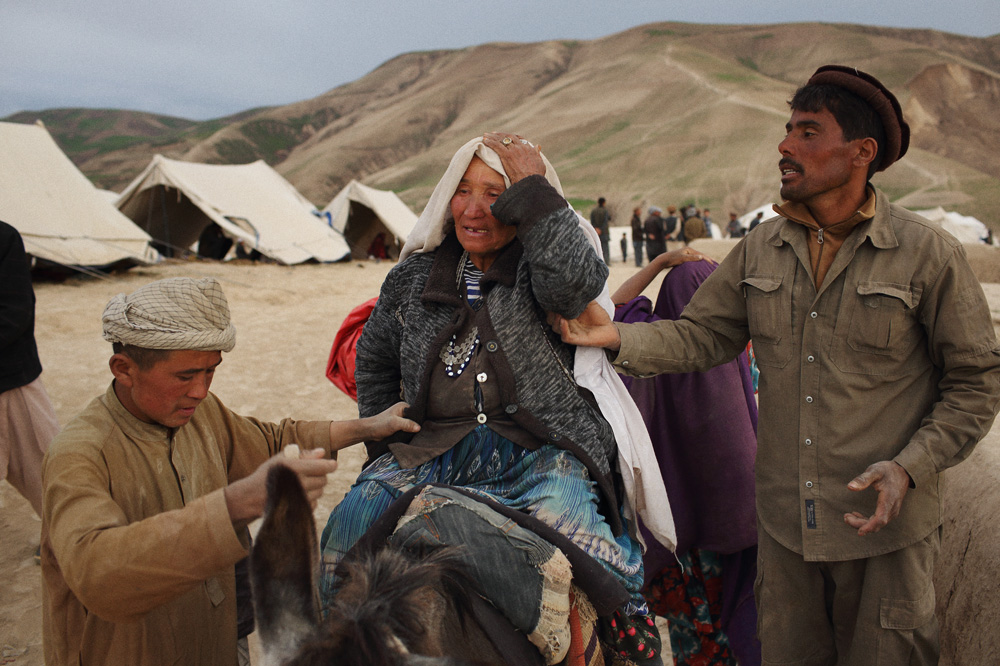 A man and young boy helped a distraught, elderly lady along on the back of a donkey, May 3, 2014.