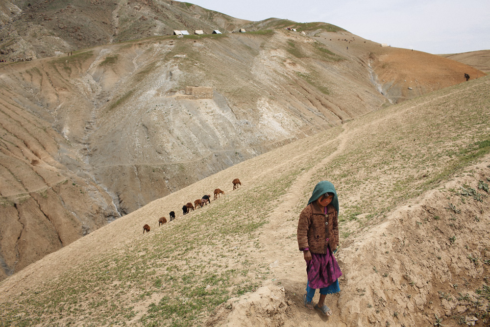 A young girl walks from her temporary tent home on the ridge beyond while a young boy herds goats across the side of a hill close to the central aid distribution point in the village, May 4, 2014.