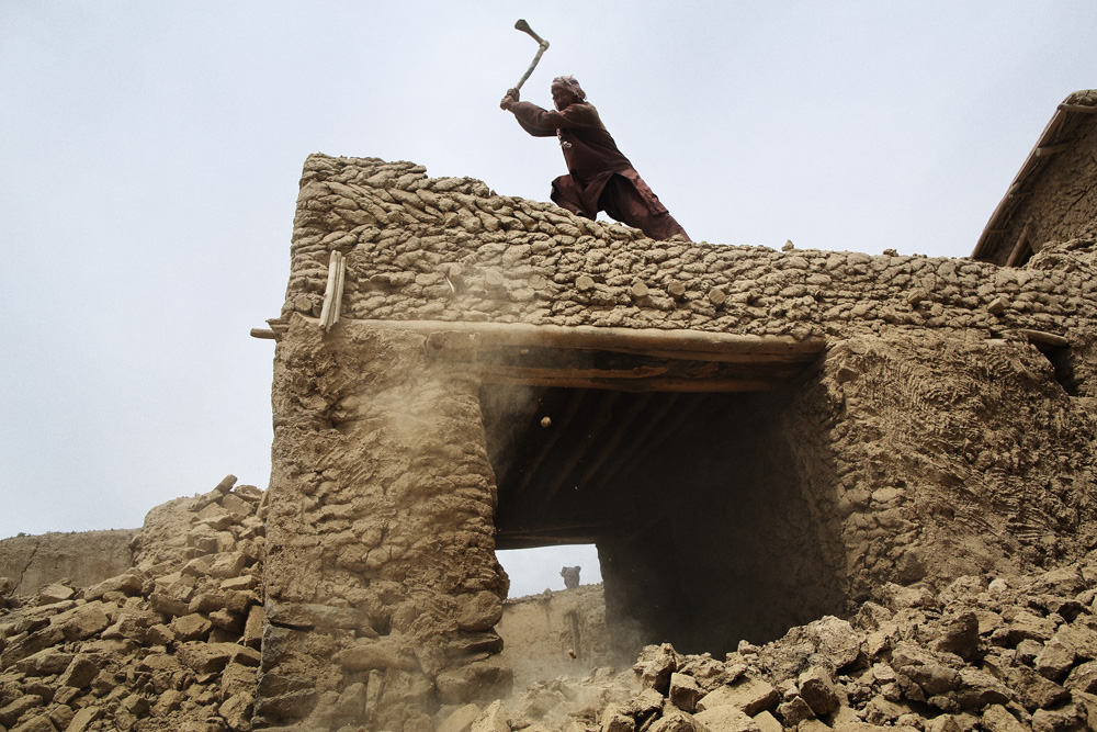 A man demolishes what remained of his home after Friday's landslide, May 4, 2014.