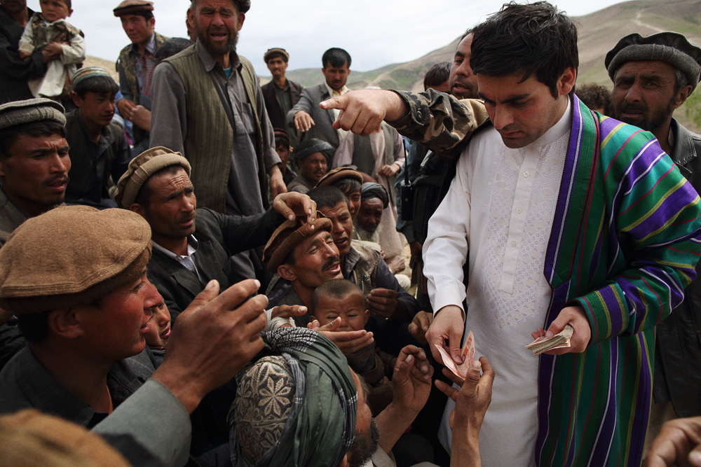 Baktash Siawash, a 28-year-old parliamentarian and former Afghan TV show host, handed out single 1000 Afghani bills (approx. $US20) to locals, until he became angered by the behavior of the crowd and left with hundreds of men, women and children giving chase, May 4, 2014.