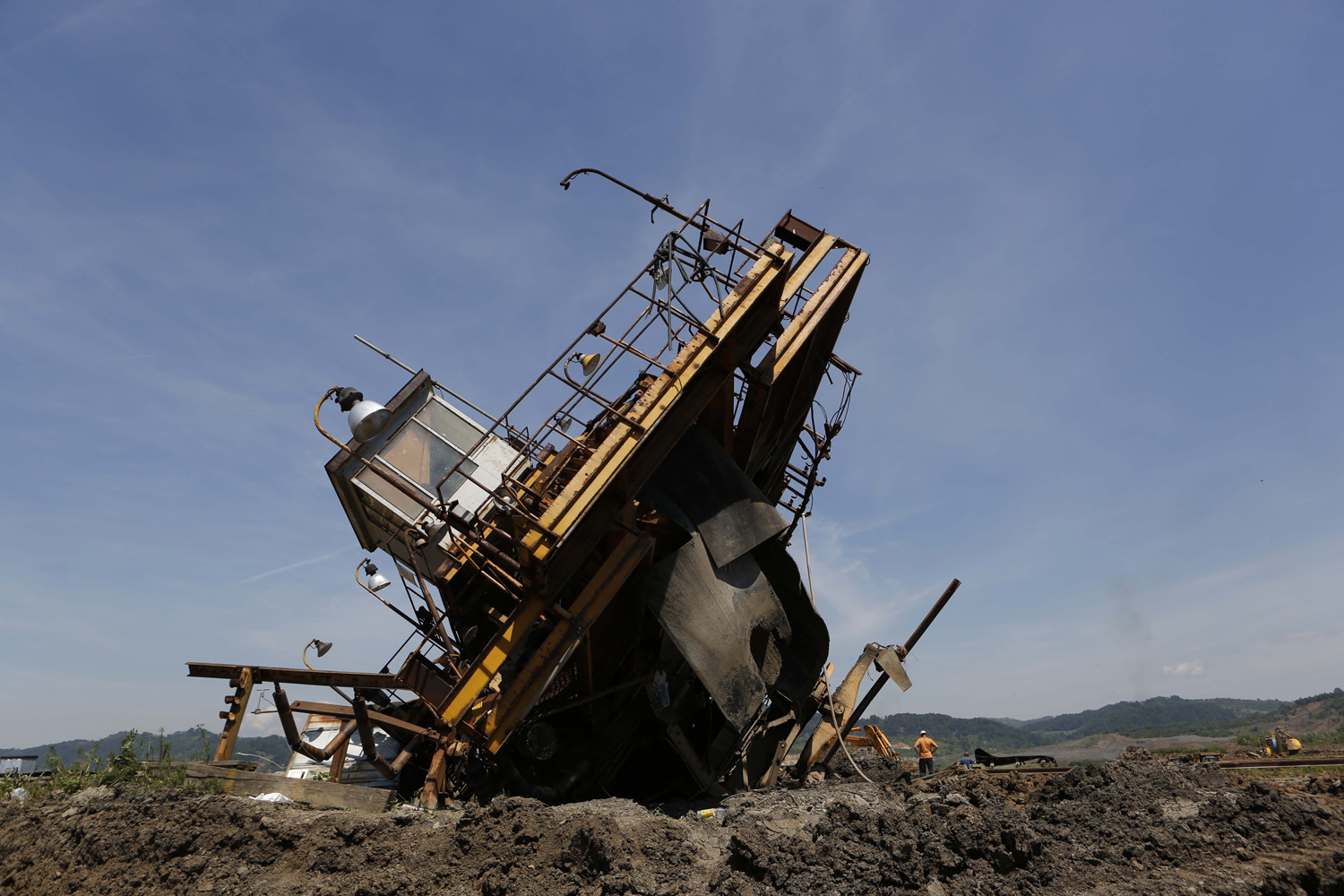 May 22, 2014. Bosnian workers inspect the damage on heavy machinery after devastating flooding at a coal mine  in the village of Sikulje near the Bosnian town of Lukavac.