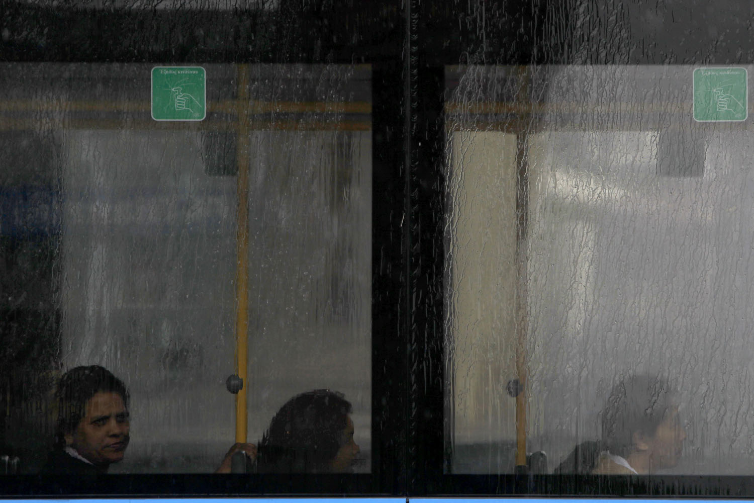 May 8, 2014. Immigrant women sit in a moving bus with rain streaking across the window during heavy rain fall in the Cypriot capital Nicosia.
