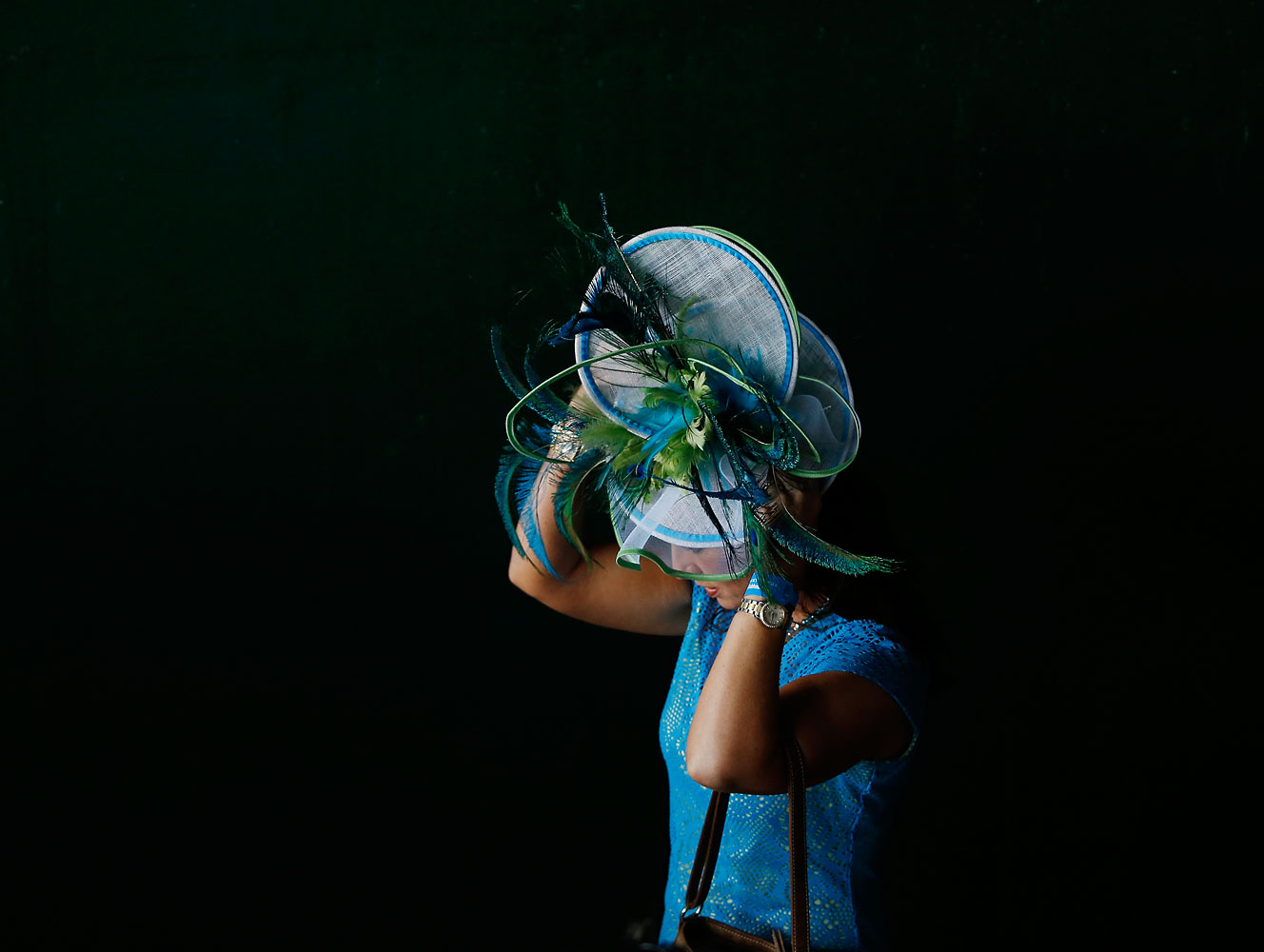 A woman fixes her Derby hat while headed to the track before the 2014 Kentucky Derby.