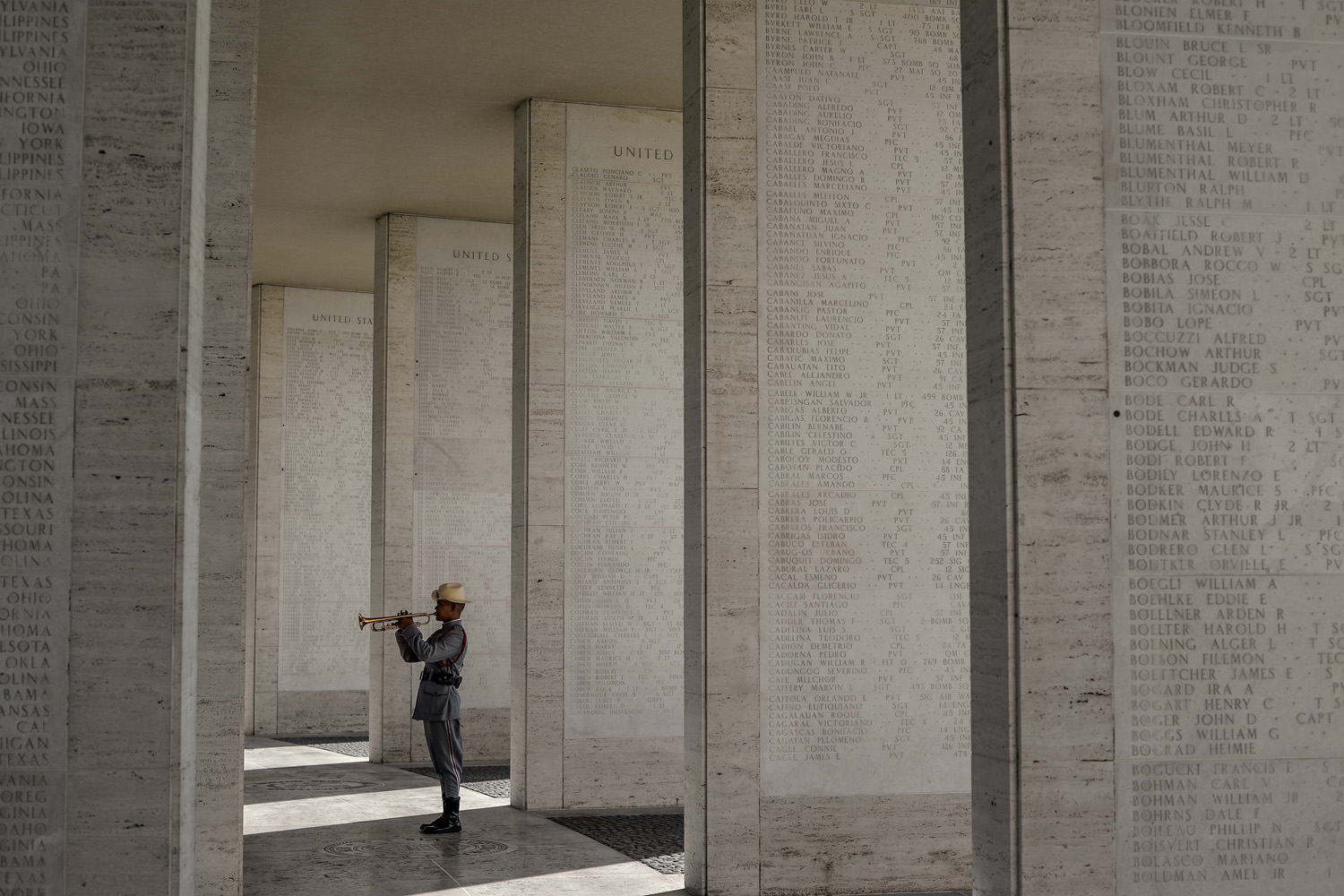 25 May 2014,  A Philippine soldier plays his bugle along the halls displaying the engraved names of soldiers who fell during World War II at a service to mark the US Memorial Day at the Manila American Cemetery in Fort Bonifacio in Taguig, east of Manila, Philippines.