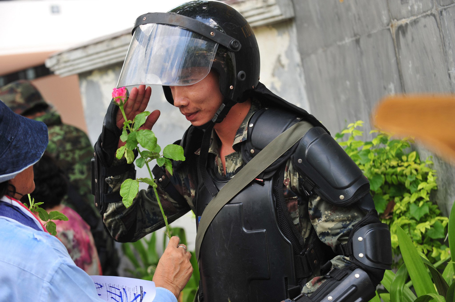 A Thai army soldier receives a flower from a military coup supporter in Bangkok on May 27, 2014.