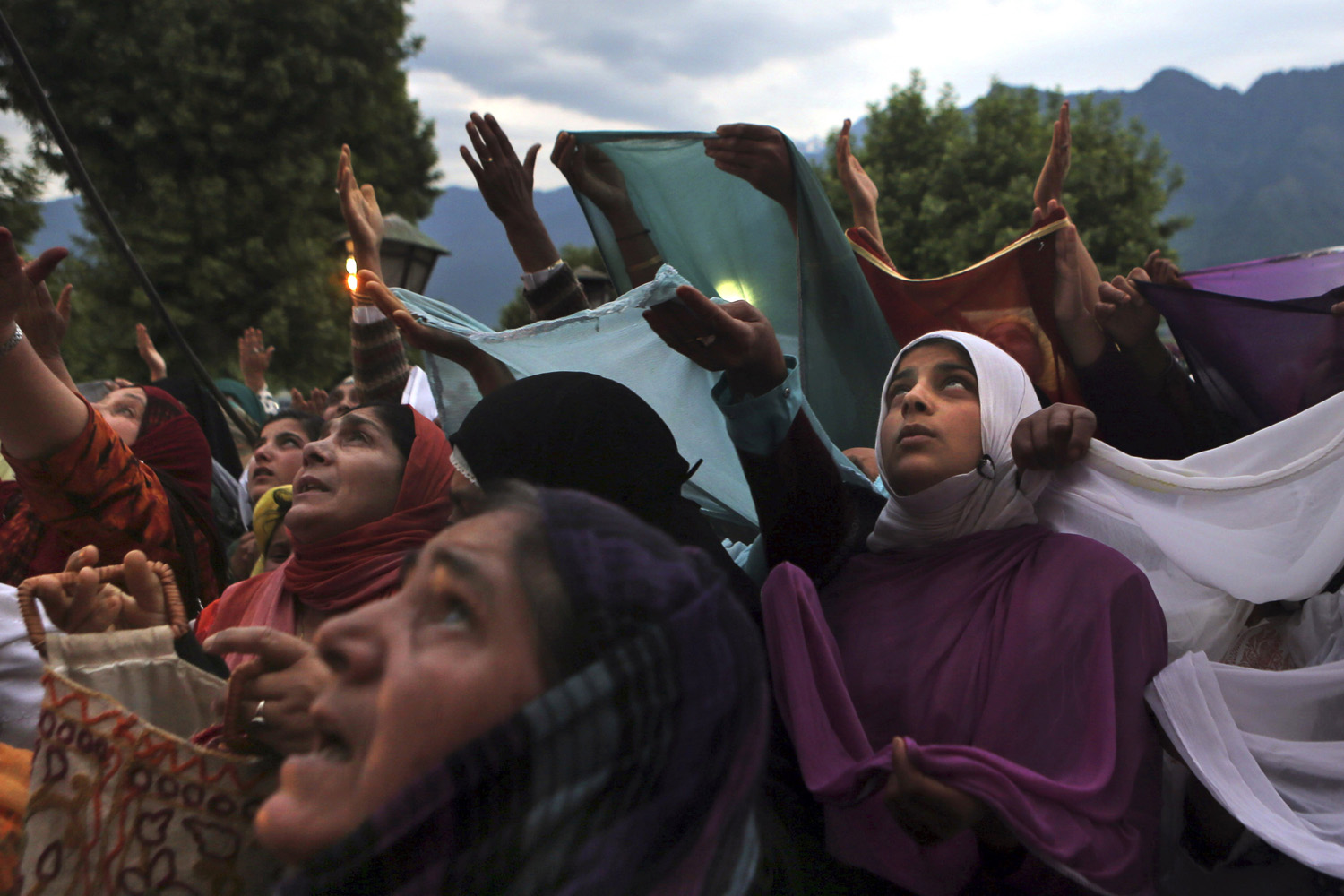 May 30, 2014. Kashmiri Muslim women devotees pray as a head priest displays a holy relic believed to be the hair from the beard of Prophet Mohammed, on Mehraj-u-Alam, at the Hazratbal Shrine on the outskirts of Srinagar, India.