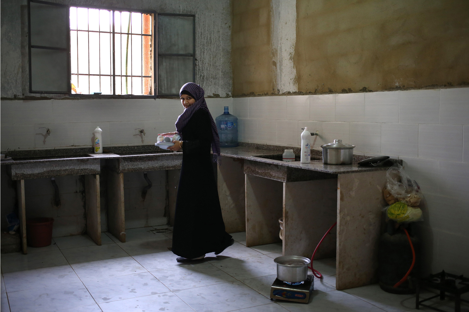 May 29, 2014. A Syrian refugee woman carries plates after she washed them in a shared kitchen in a collective center where many Syrian refugees live, in Kirbet Daoud village in Akkar, north Lebanon.