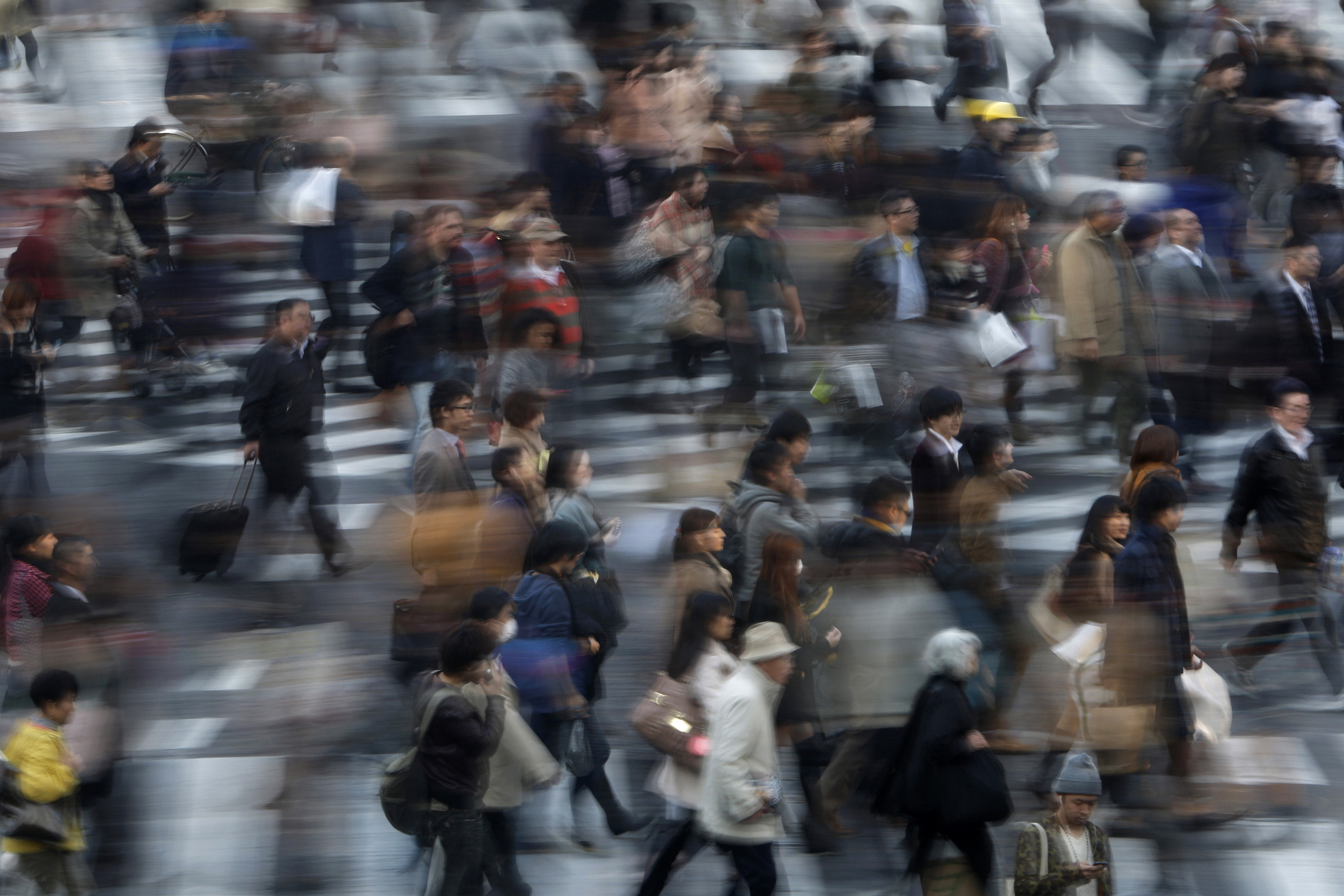 Pedestrians cross an intersection in the Shibuya district of Tokyo, Japan, on Friday, Nov. 22, 2013.