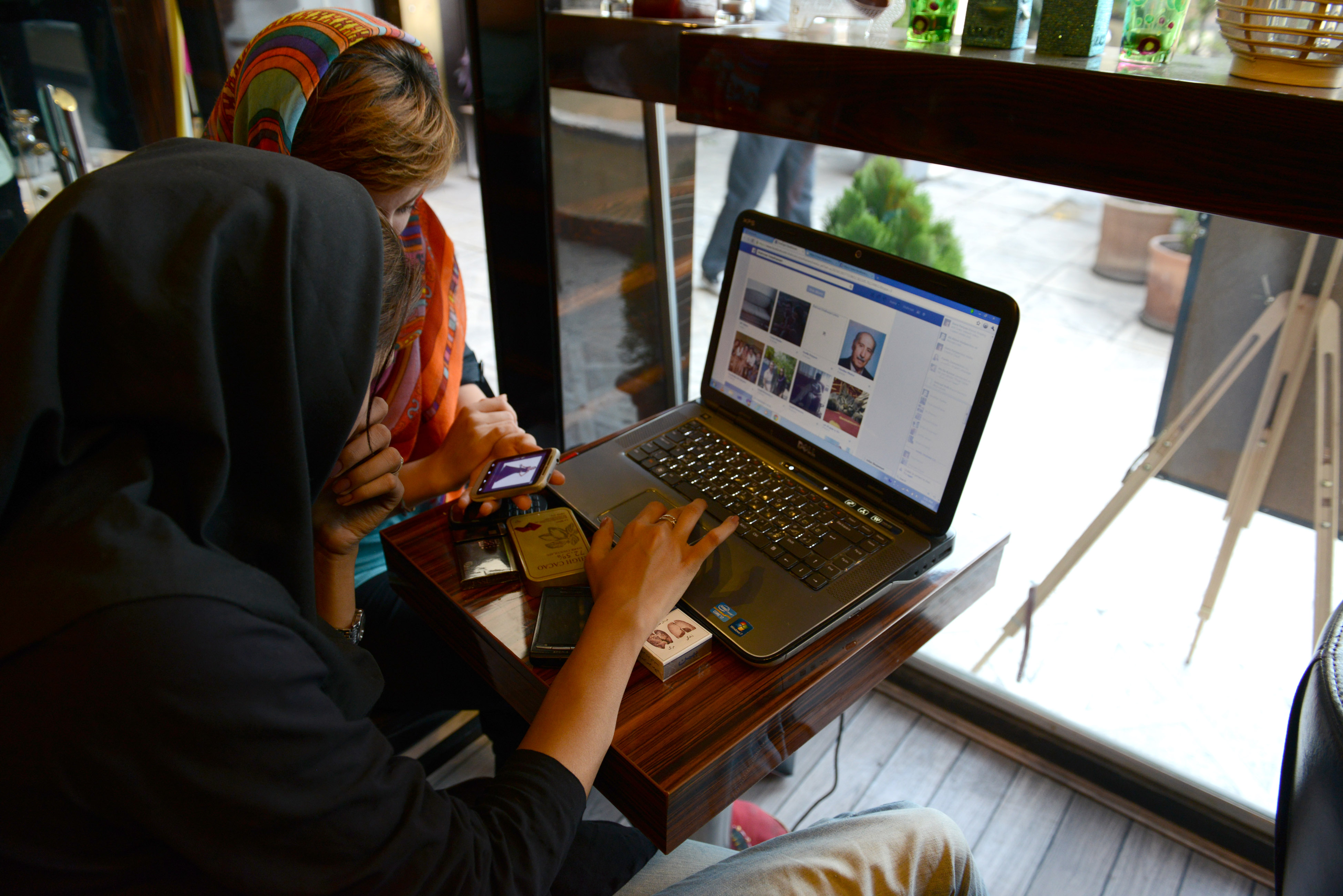 Two girls sit in a north Tehran coffee shop using Facebook and looking on the mobile phone at online fashion clothing in Tehran, Iran on October 13, 2013.