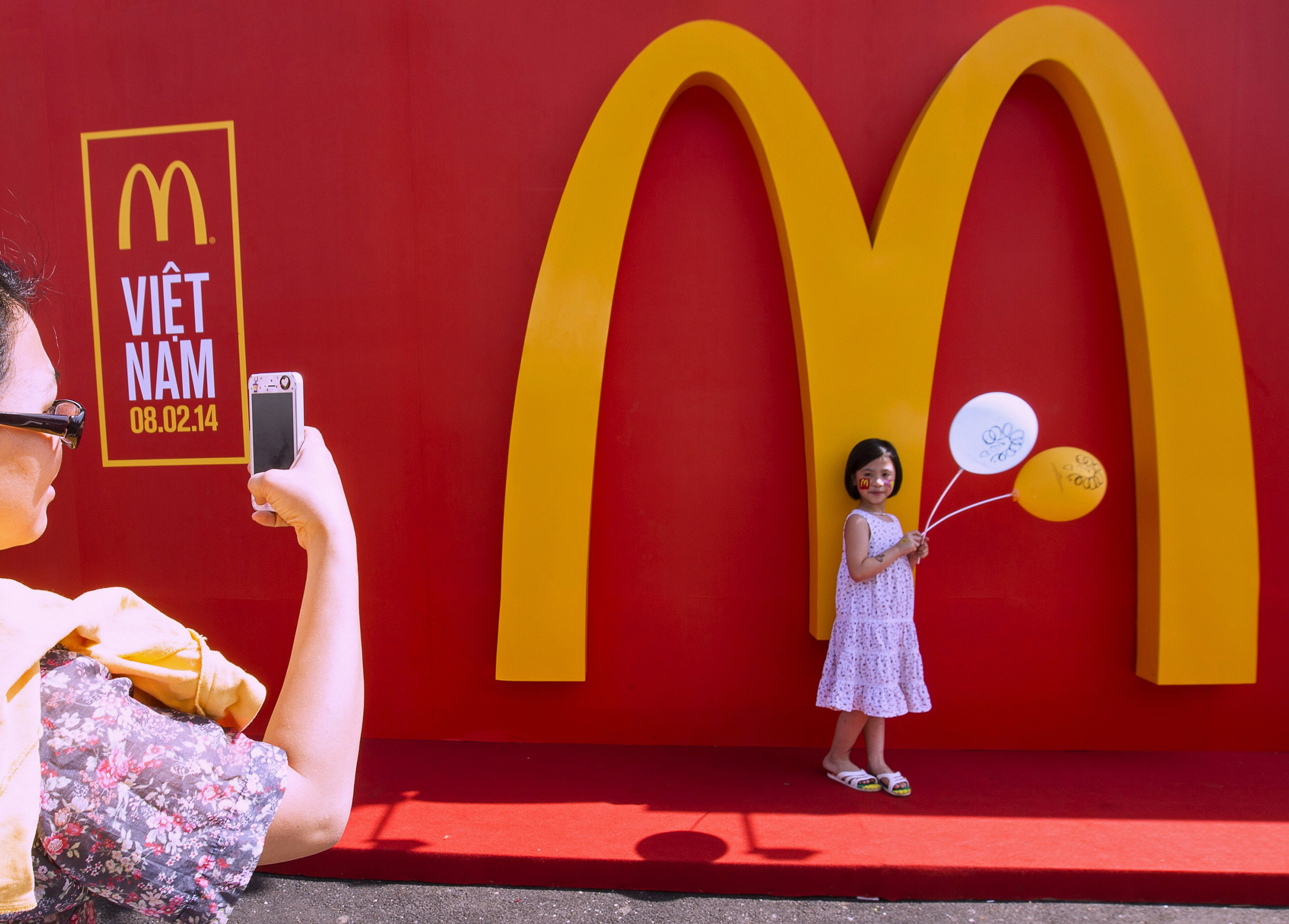 A mother takes a picture of her daughter in front of the Golden Arches during the opening ceremony of Vietnam's first McDonald's restaurant in Ho Chi Minh City on Feb. 8, 2014