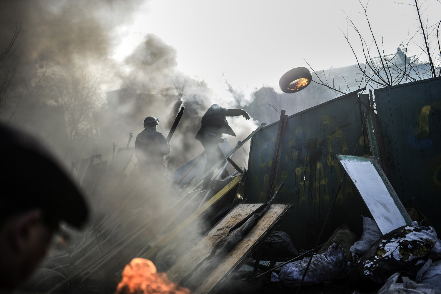 An anti-government demonstrator throws a burning tire as he build a barricade on February 21, 2014 at the Independent square in Kiev.