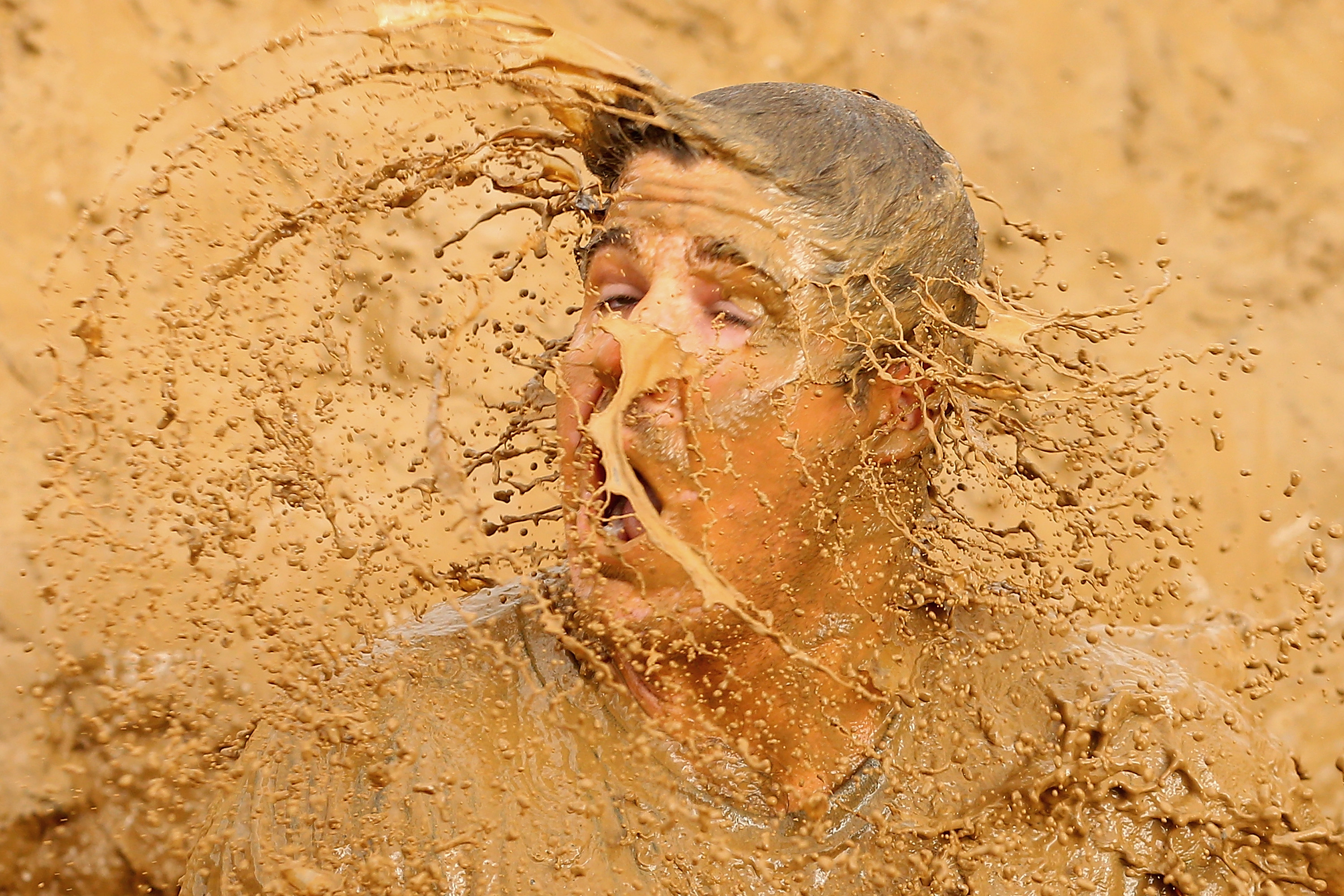 A competitor falls into muddy water during Toughmudder at Phillip Island Grand Prix Circuit on March 22, 2014 in Phillip Island, Australia.