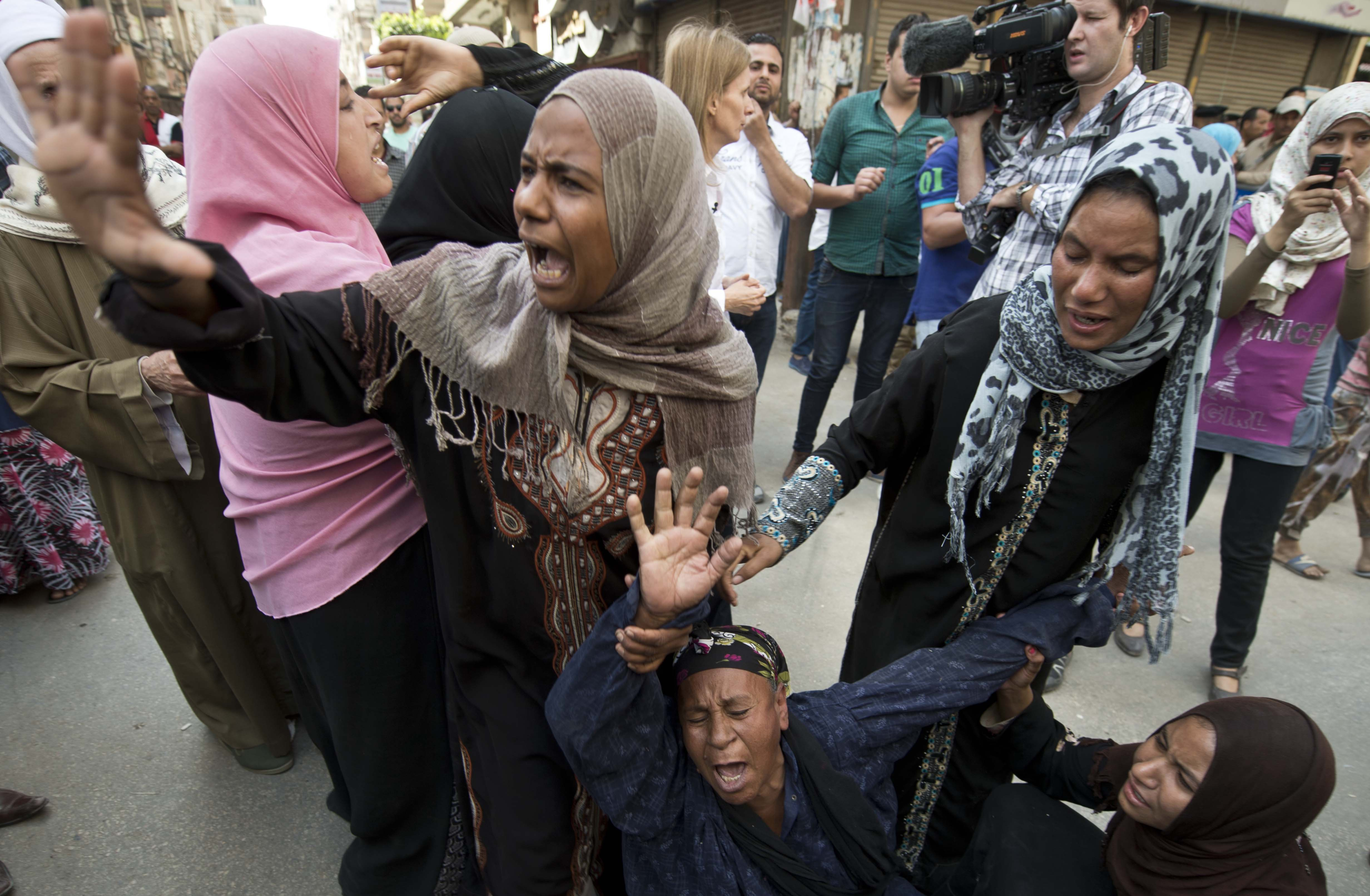 Egyptians react outside the courtroom in Egypt's southern province of Minya after an Egyptian court sentenced Muslim Brotherhood leader Mohammed Badie and 682 alleged Brotherhood supporters to death on April 28, 2014