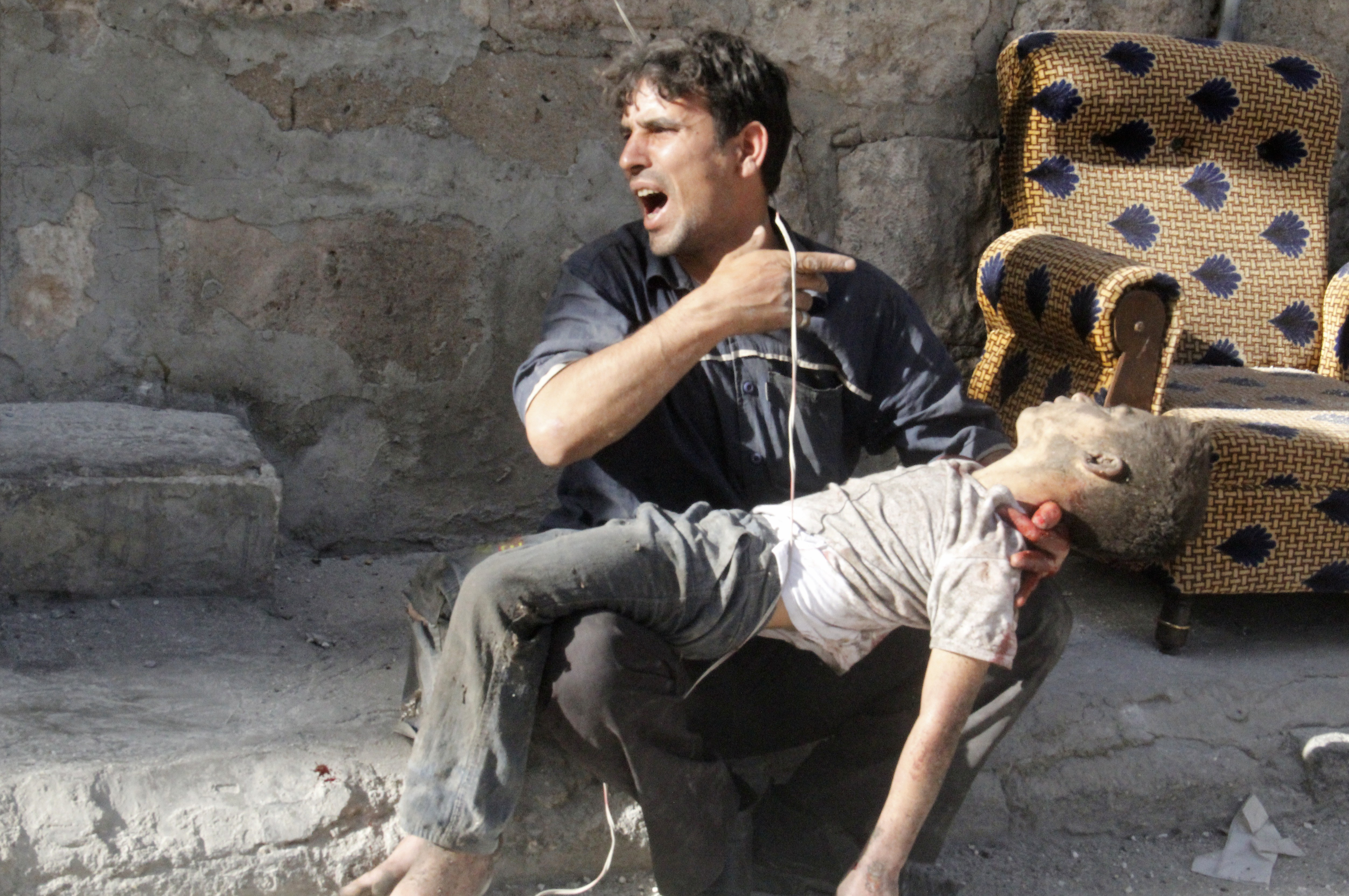 A Syrian man carries a boy's body from the site of an air strike reportedly by Bashar Assad's forces May 1 in Aleppo.